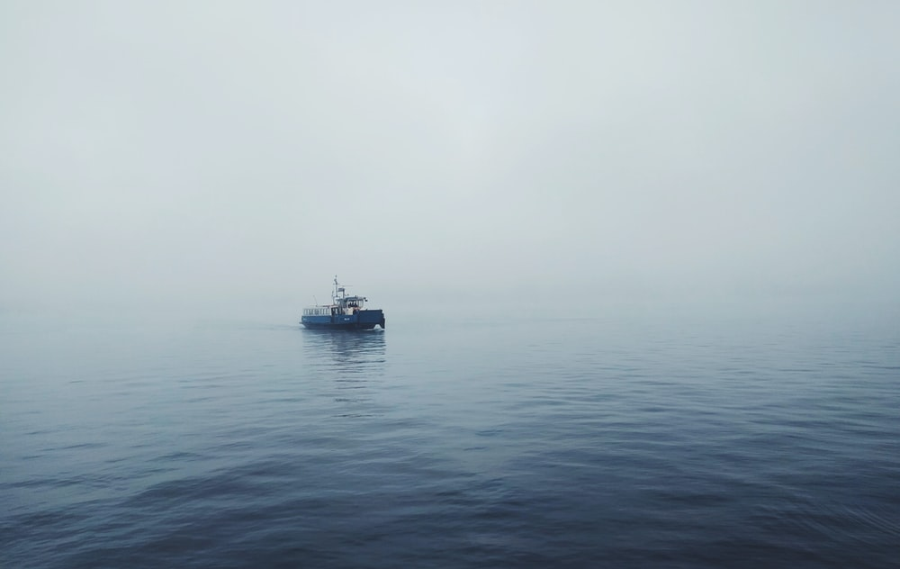 focus photo of black fishing boat on body of water