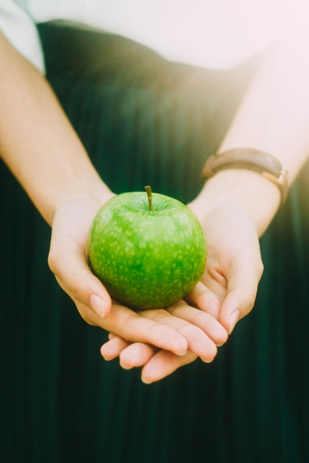 person holding green apple