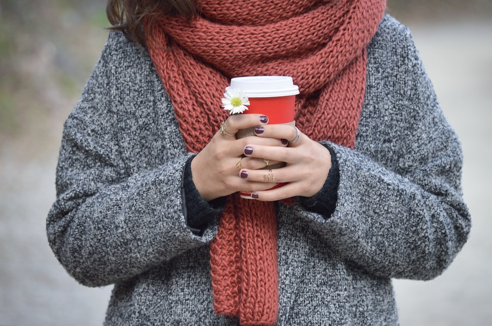 A person in a scarf and sweater holds a to-go coffee cup in both hands