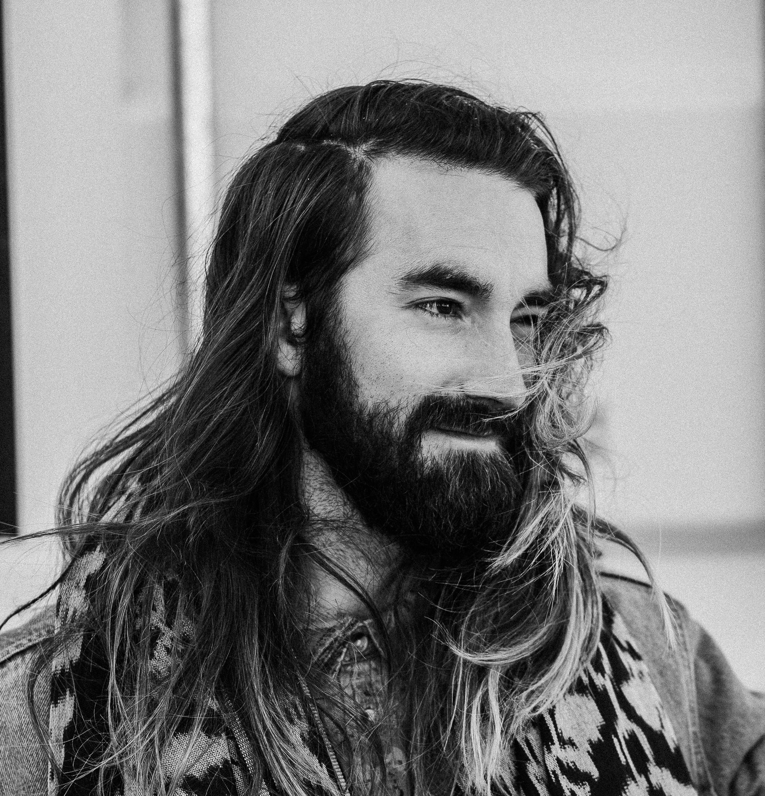 Black and white shot of man with long hair and beard