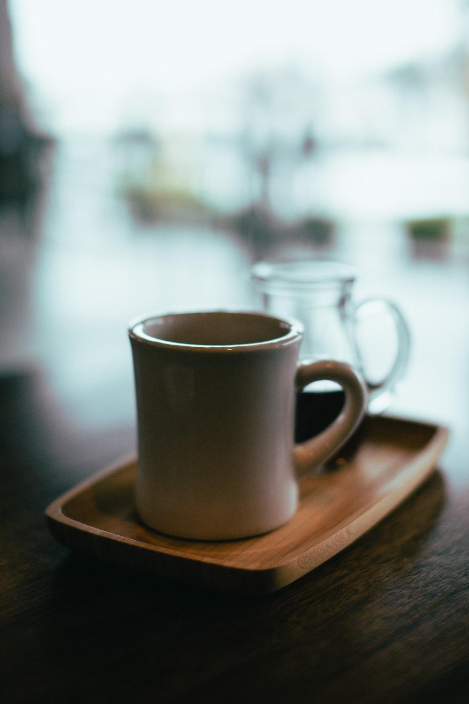 beige mug on top of brown wooden tray