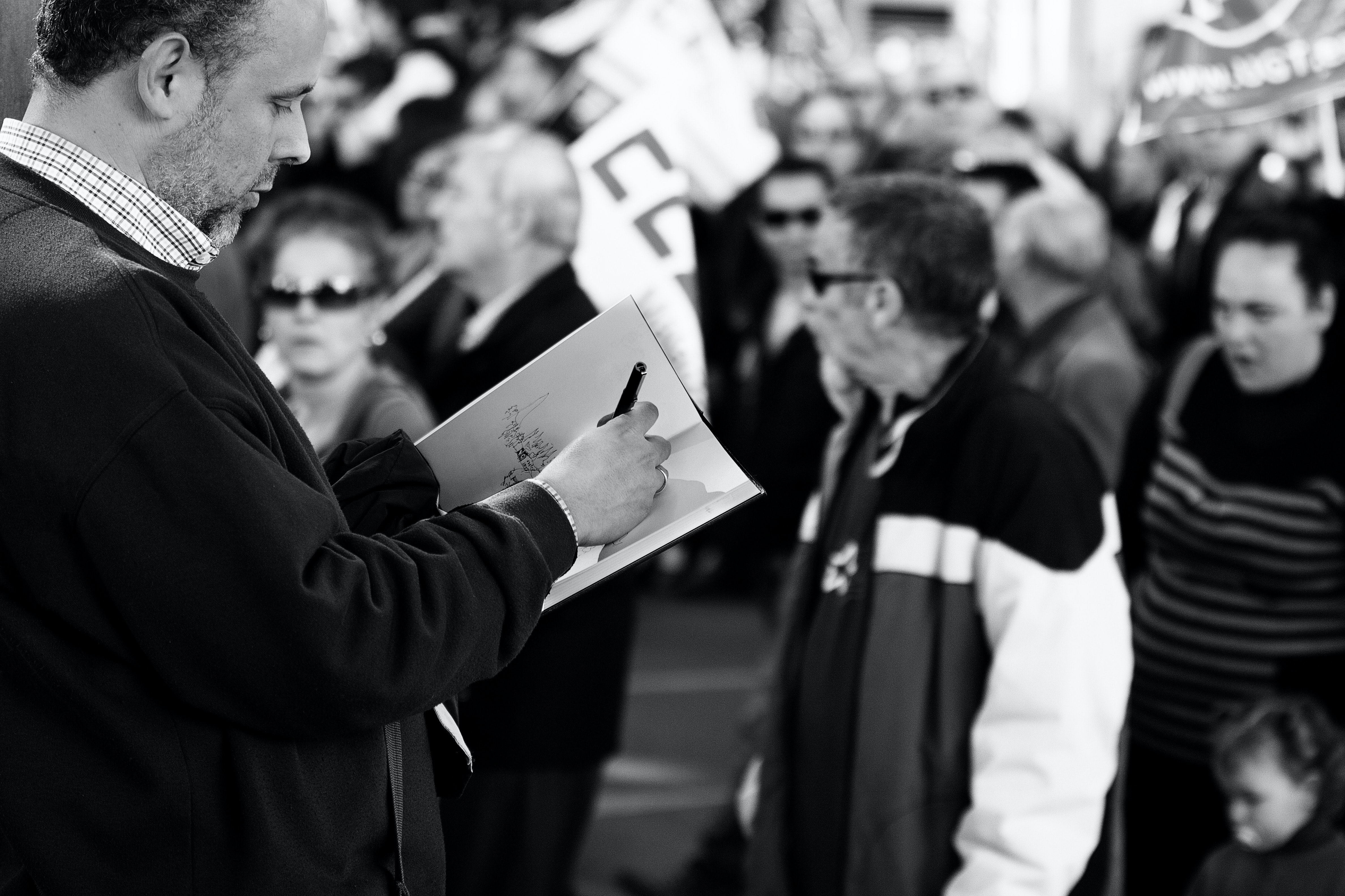 A black-and-white shot of a man scribbling in a notebook near a crowd of people