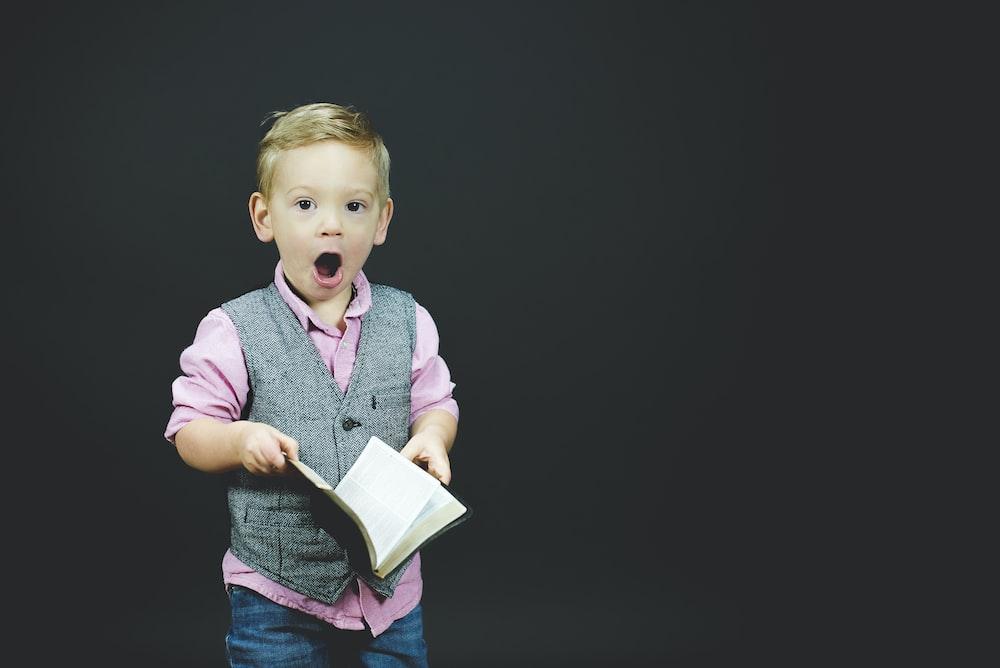 本を保持している灰色のベストとピンクのドレスシャツを着ている少年