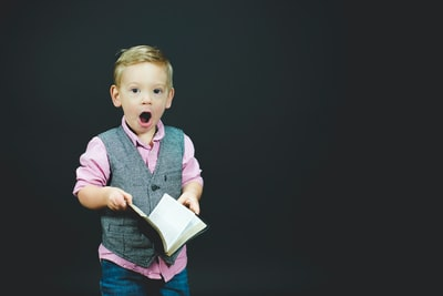 本を持って驚いている顔をしている外国人の子供の画像
