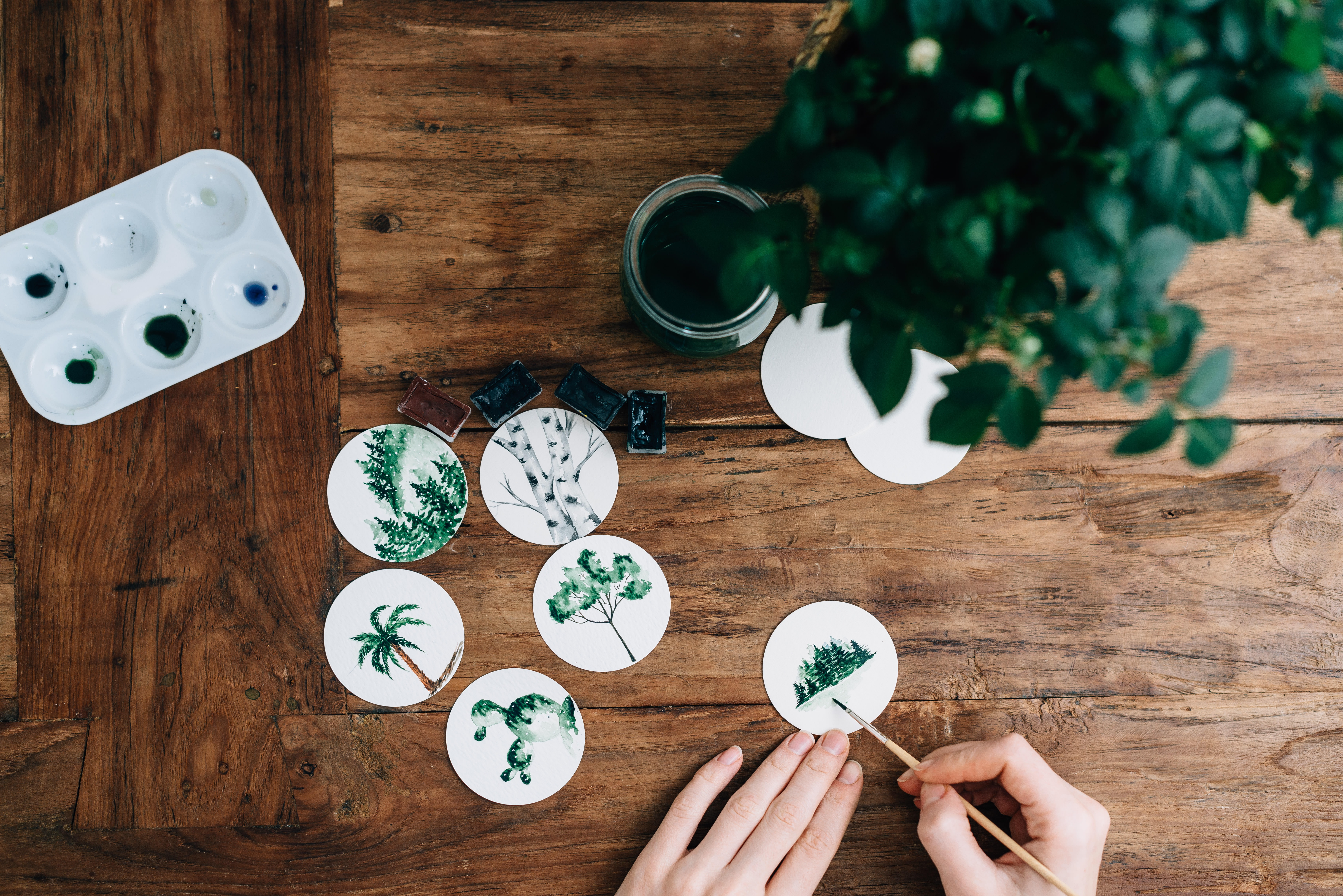 A person painting plants on small white stickers