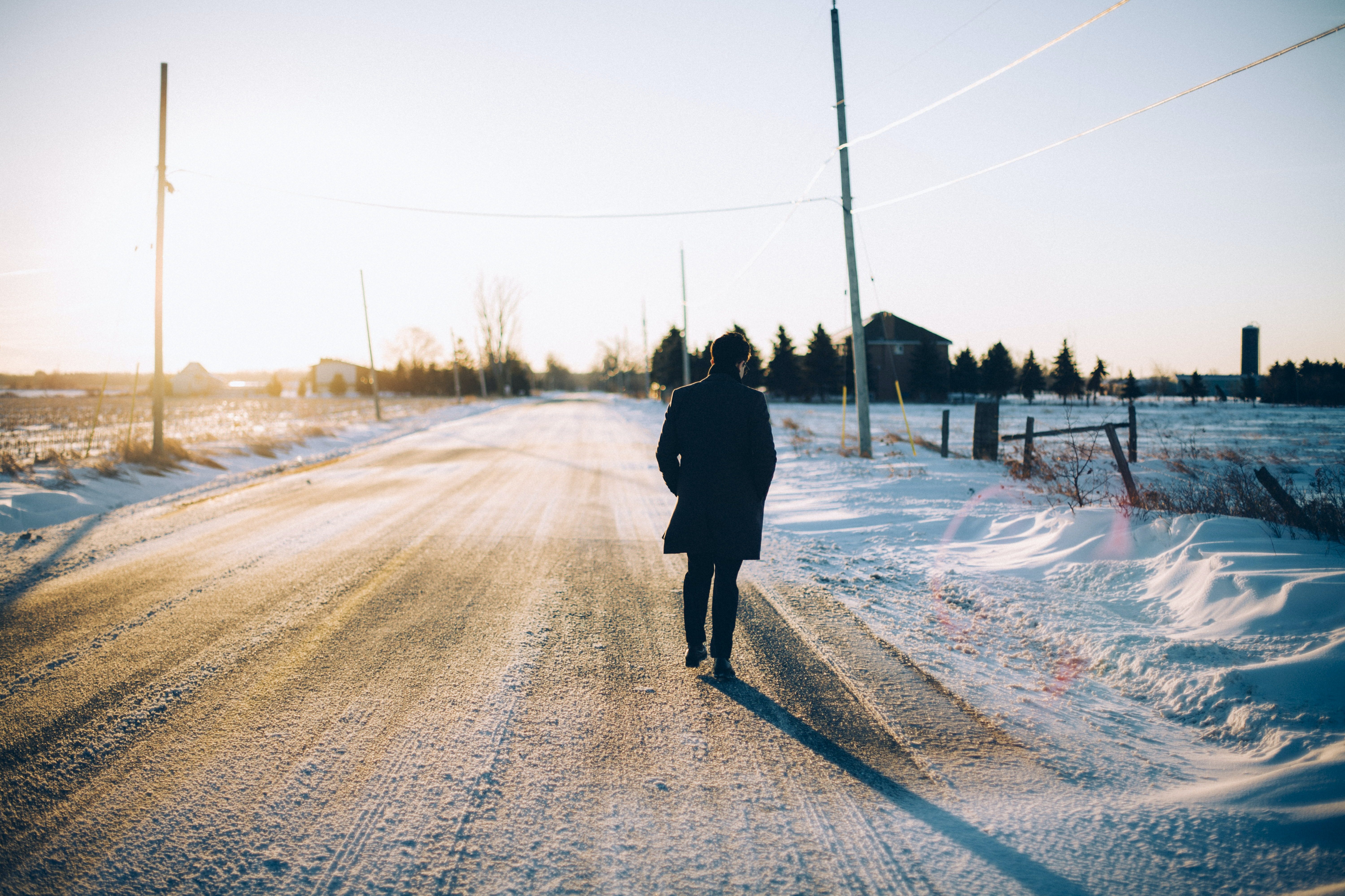A silhouette of a person walking on a snow covered road