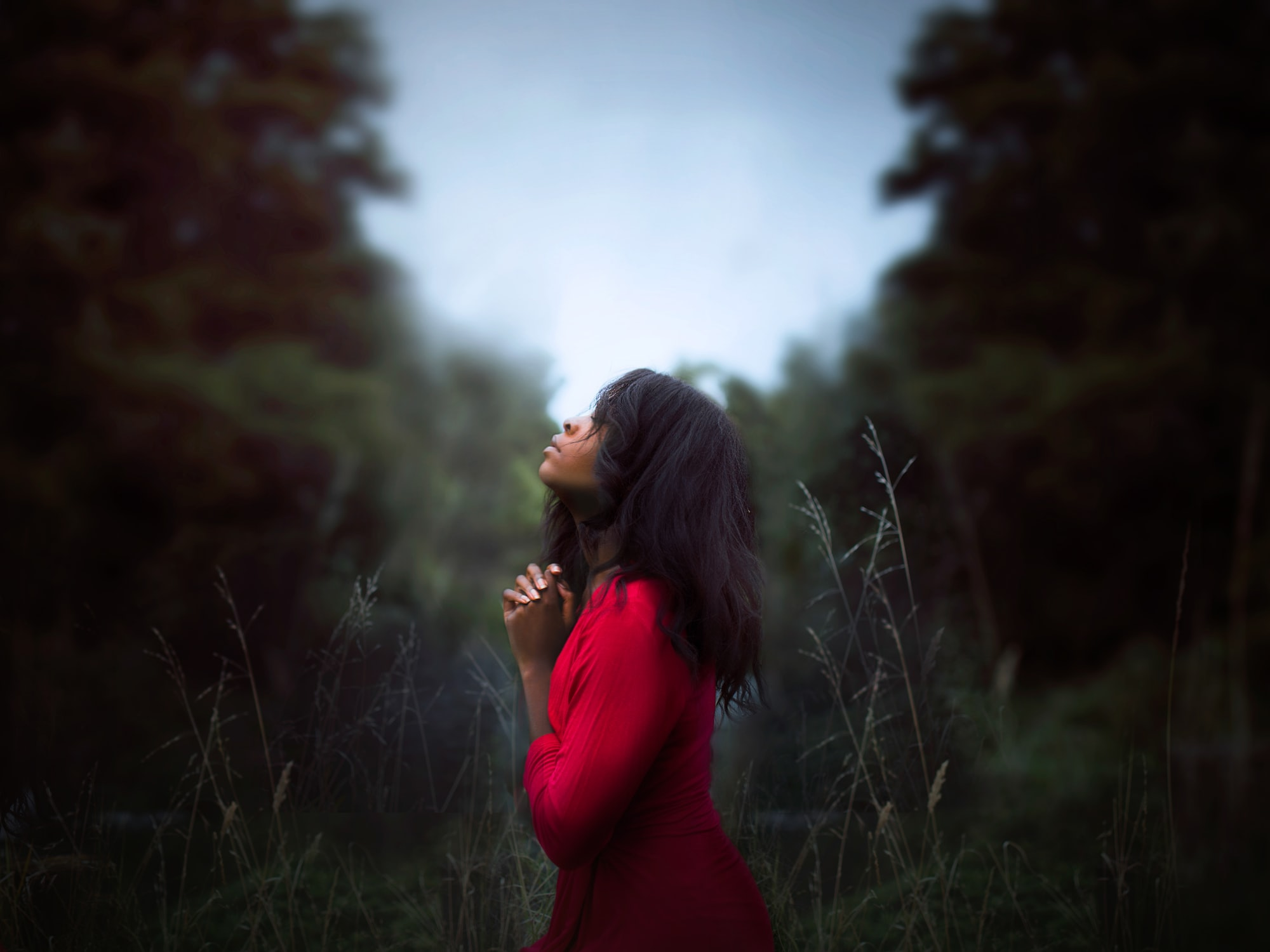 Woman holding her hands in prayer and looking up.