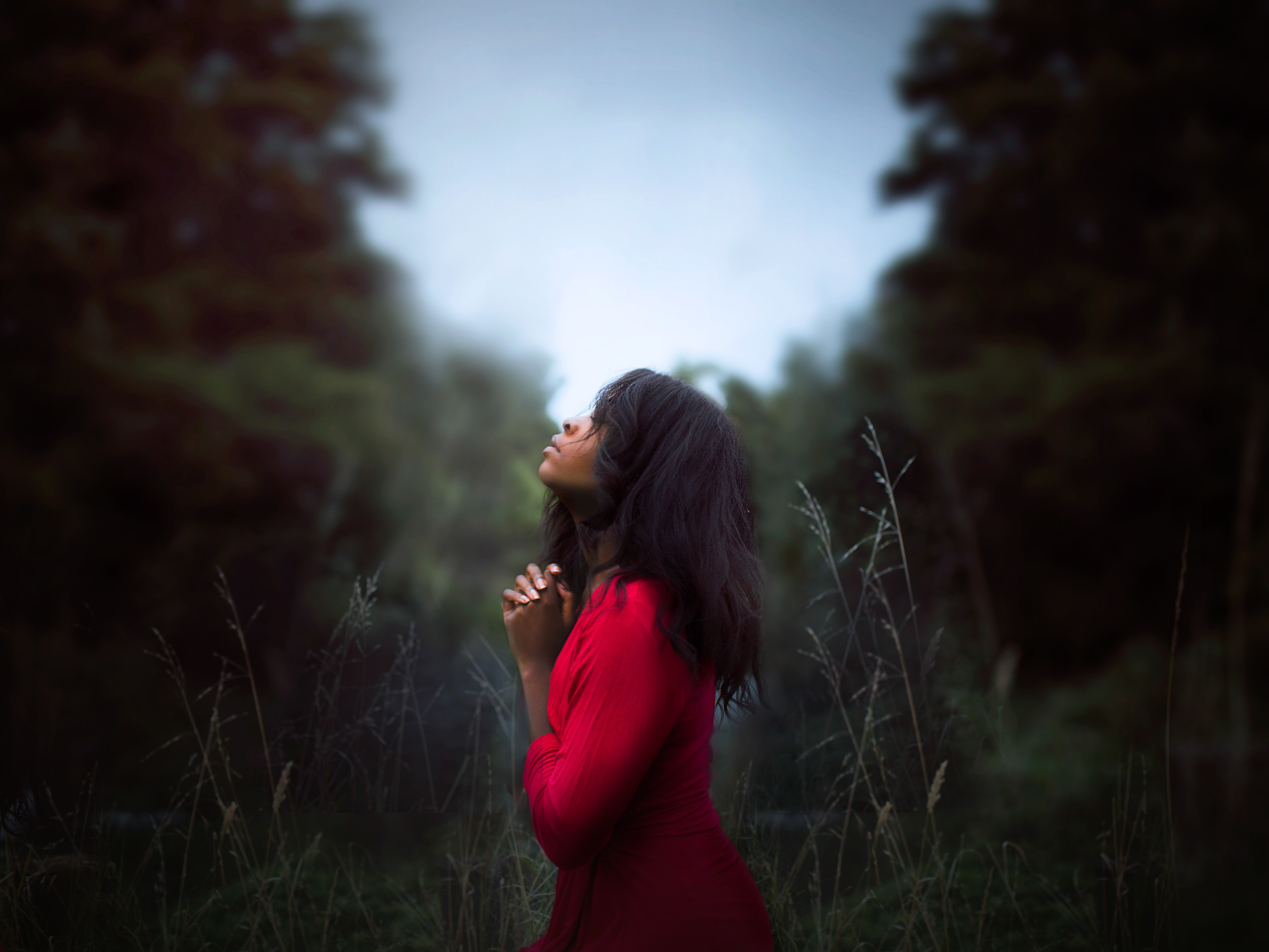 Pensive woman standing in a field praying and thinking