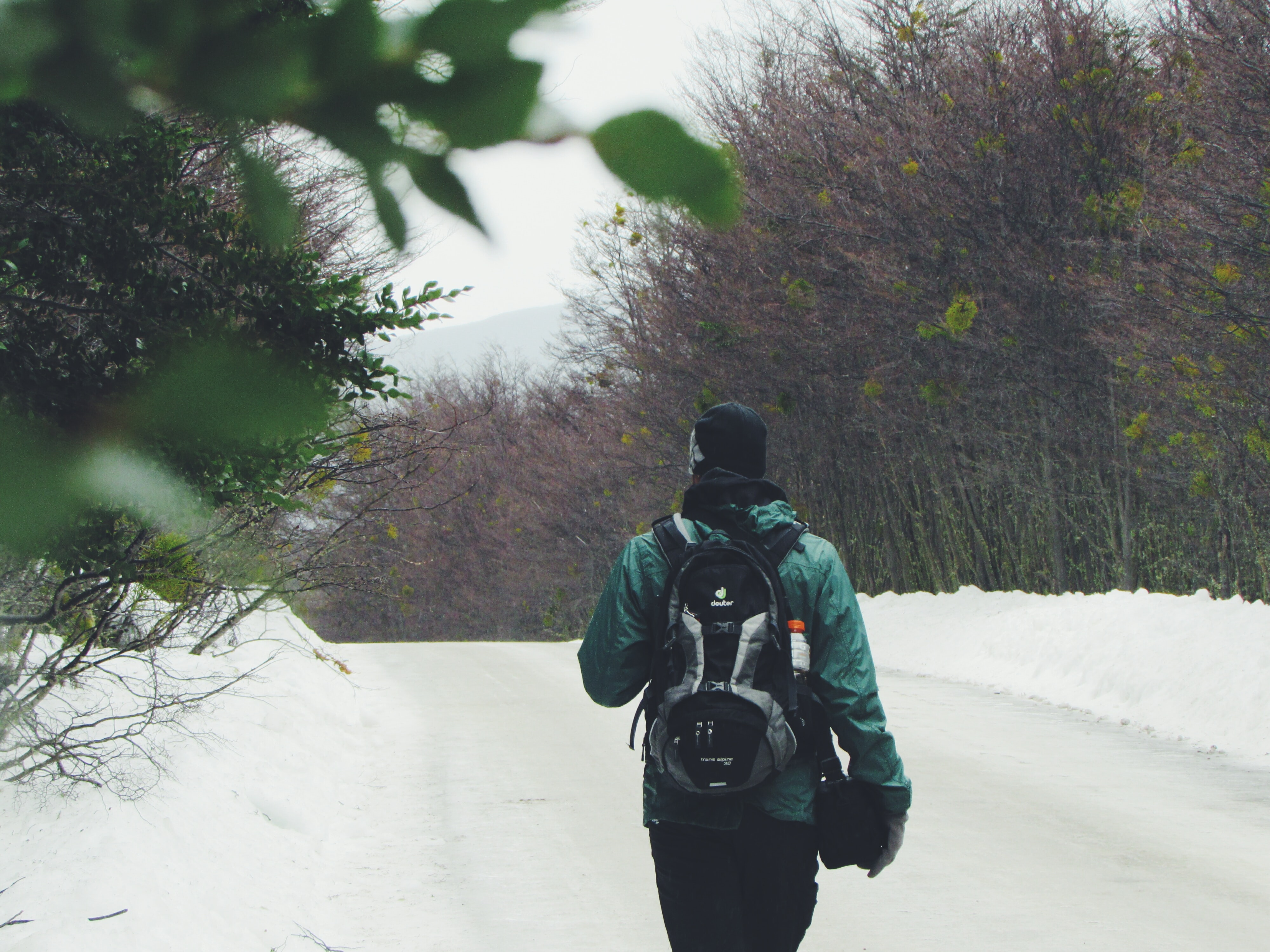 A person in a coat faces away while hiking on a snowy path in Patagonia
