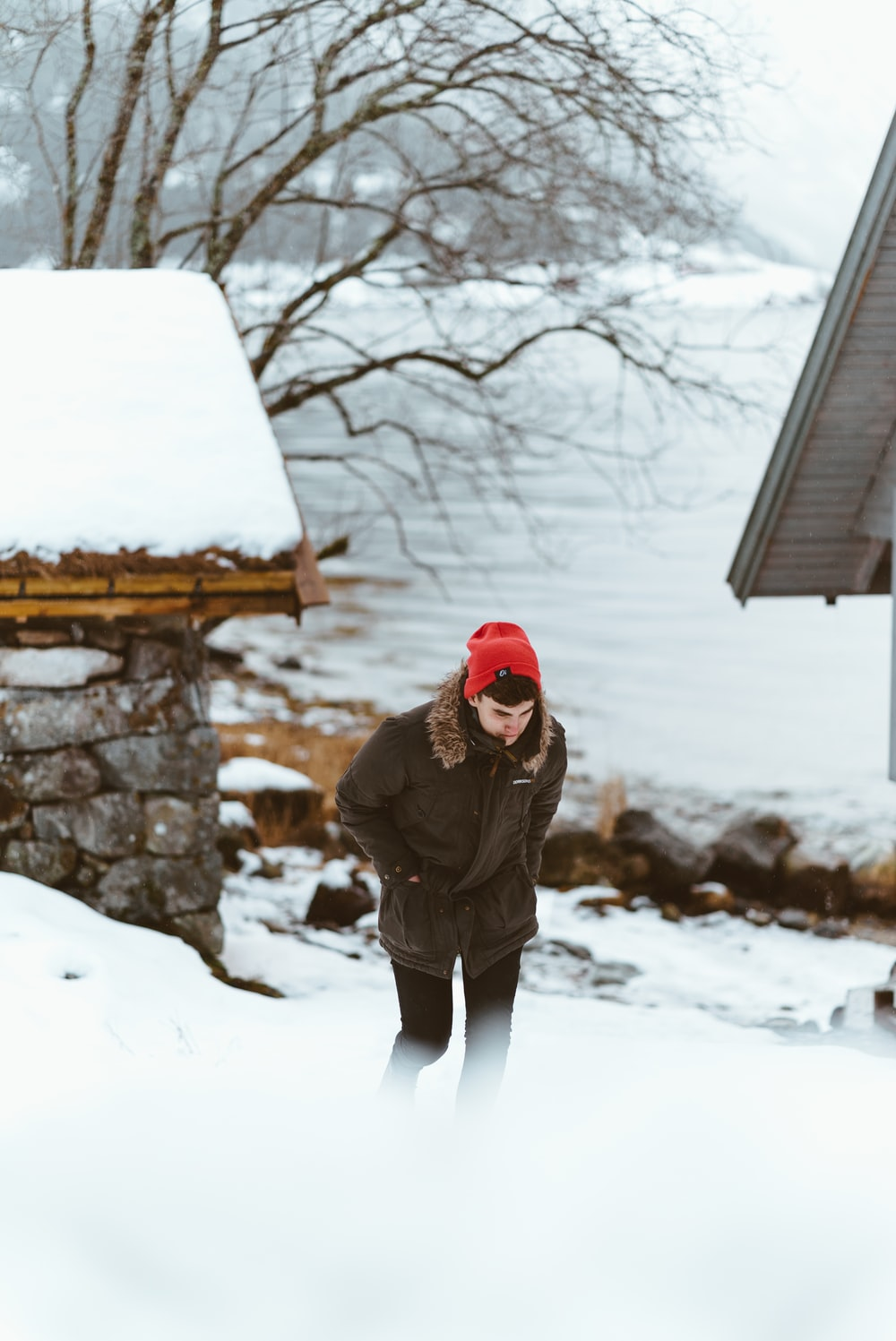 A man wearing a winter coat and beanie hat walking in the snow by a lake in Flåm