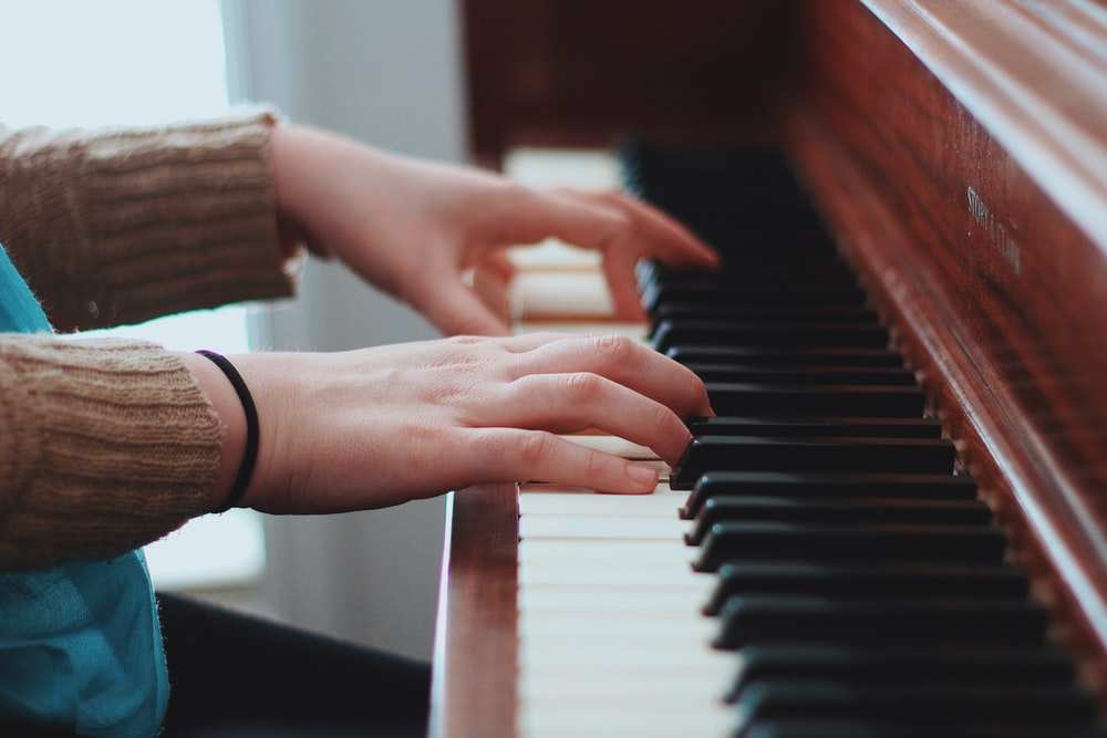 person wearing brown sweater playing piano