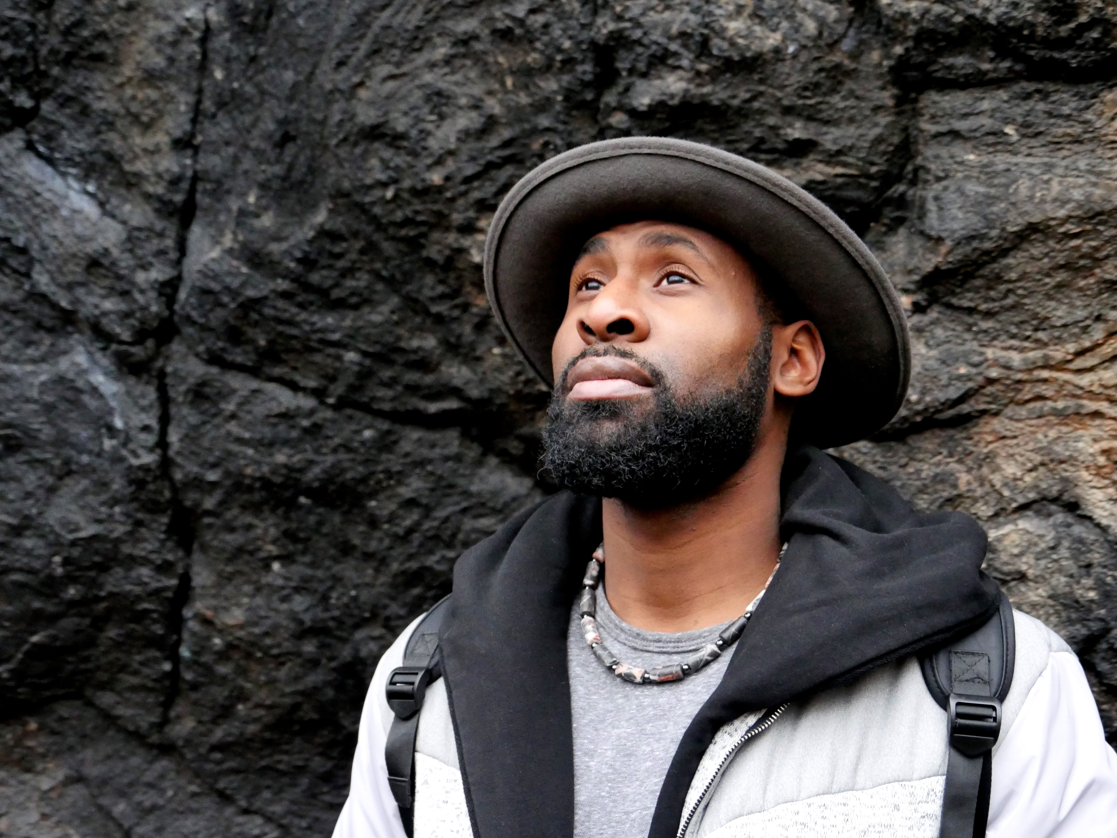 A bearded man in a brimmed hat and backpack looks upward before a rocky wall