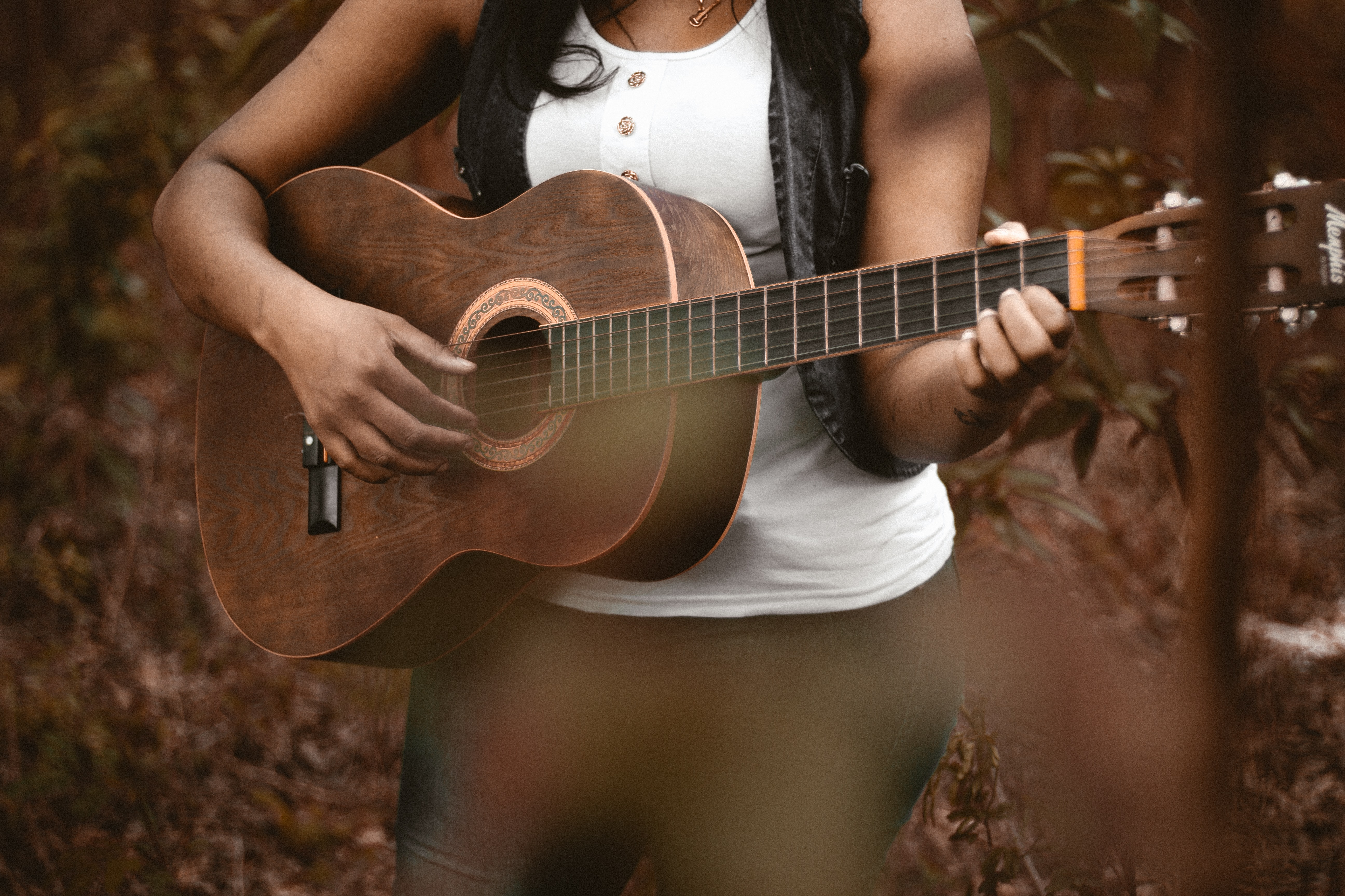 A woman playing acoustic guitar with leaf-covered ground in the background