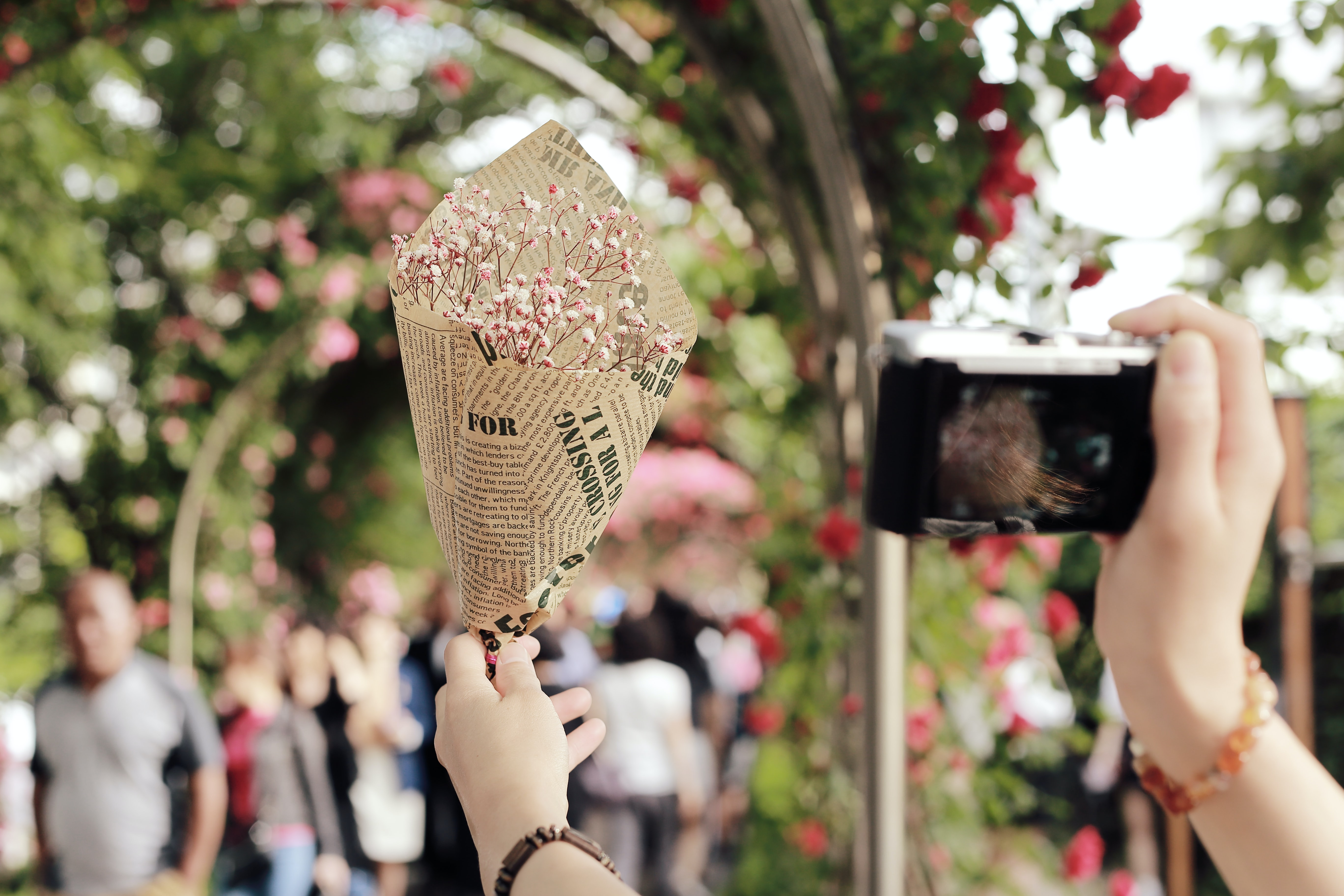 A person holding up a small posy of white flowers in one hand and taking a picture with a camera in the other hand