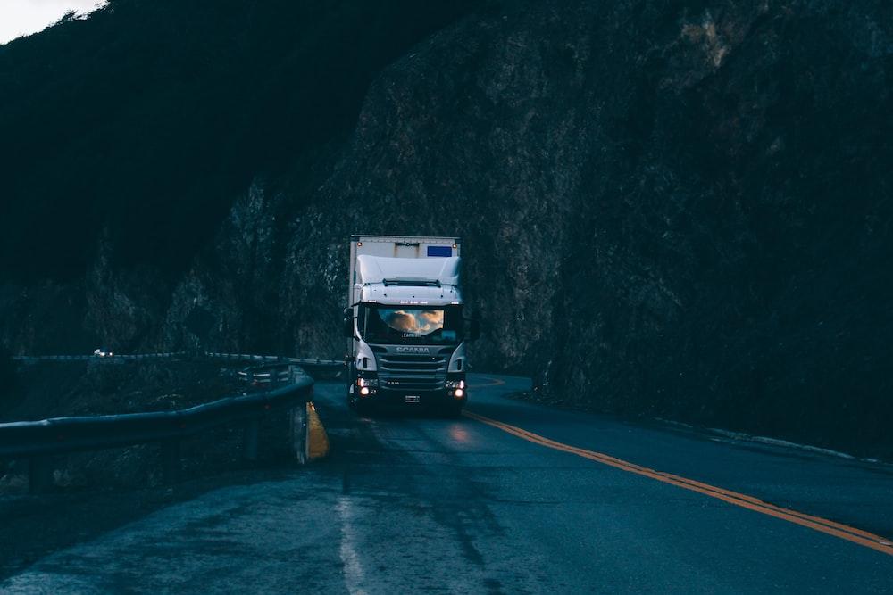 trailer truck passing on road near rail guard