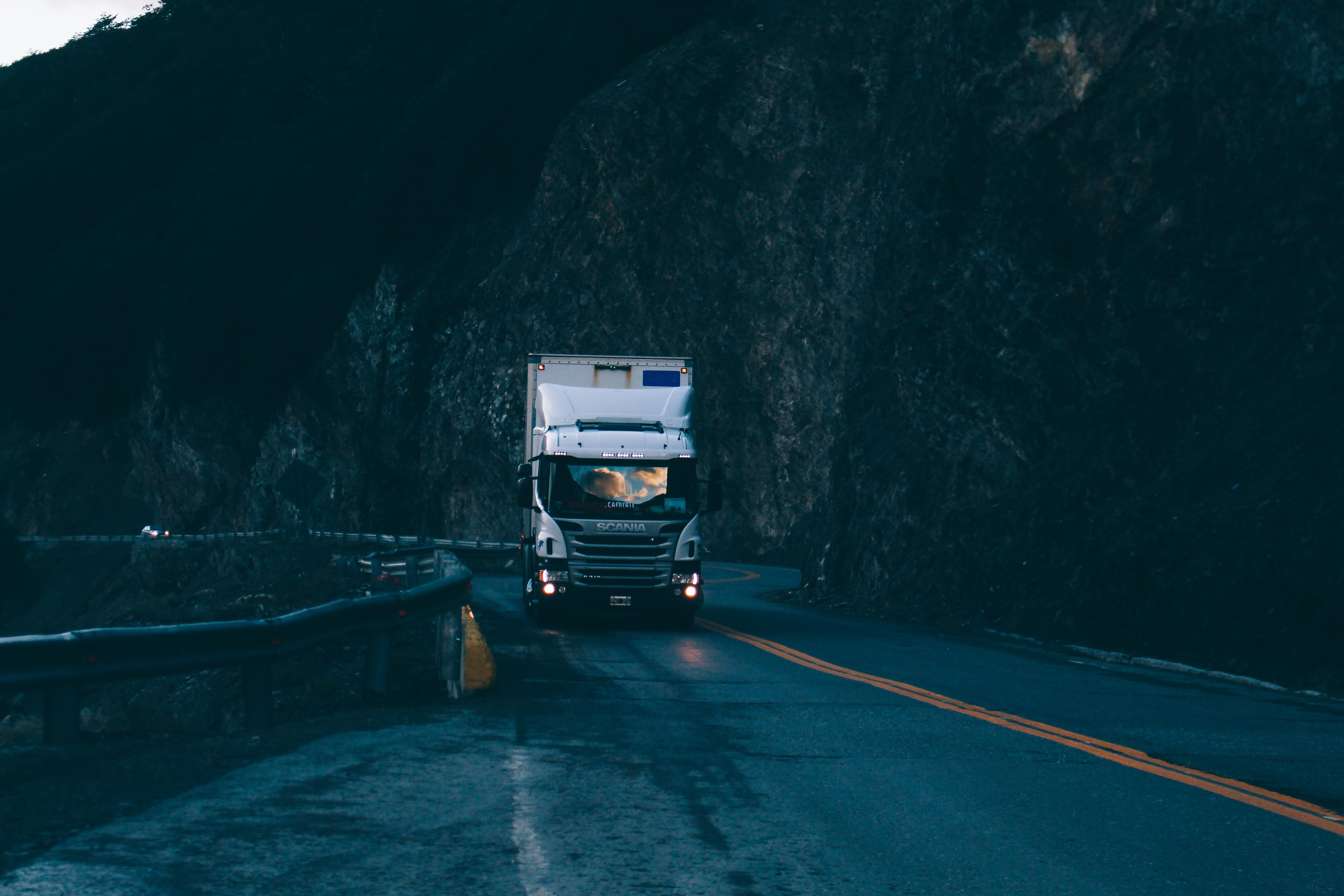 A silver Scania truck driving down an empty road in the mountains in the evening