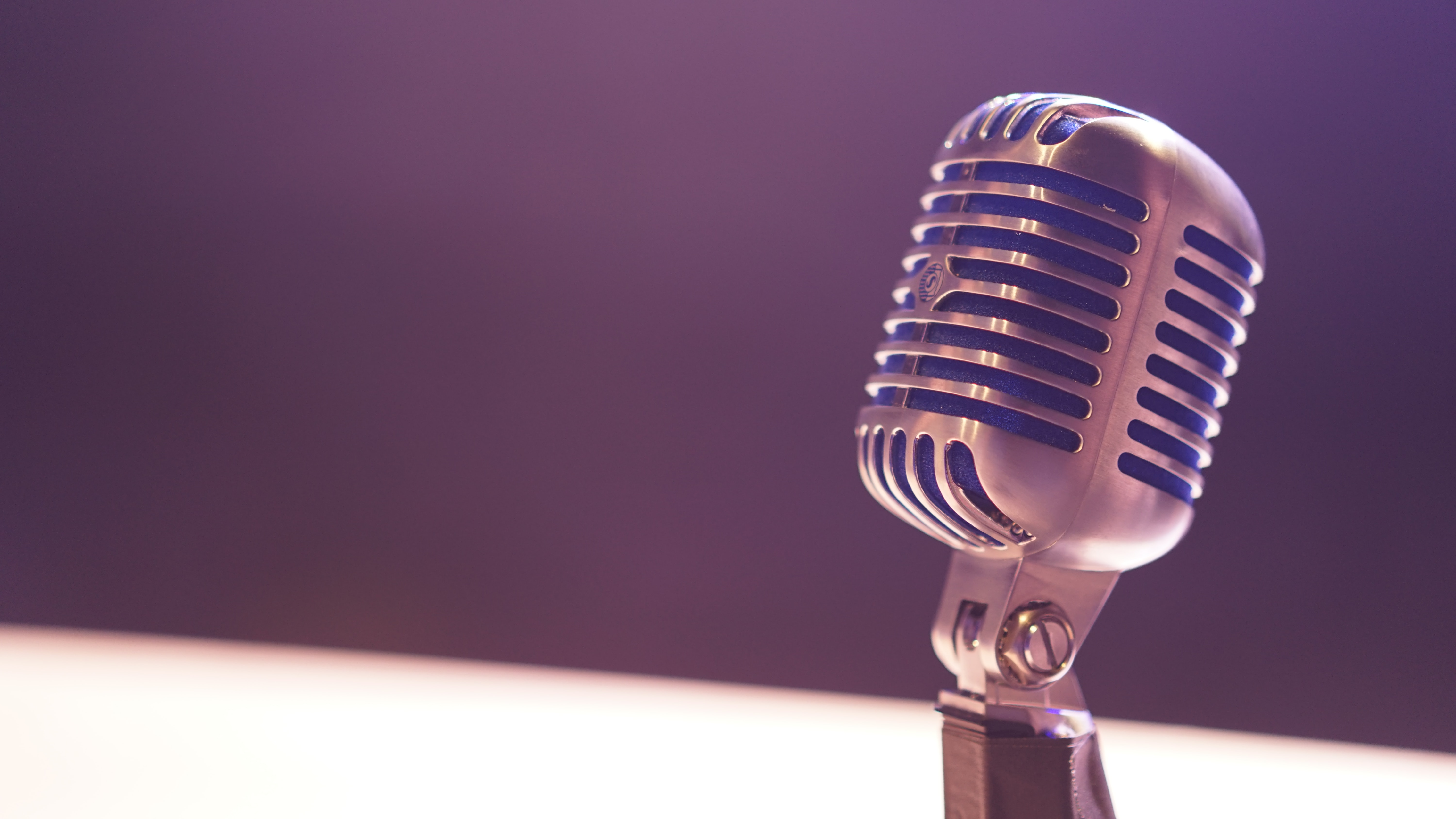 A microphone against a blurry background of white and black