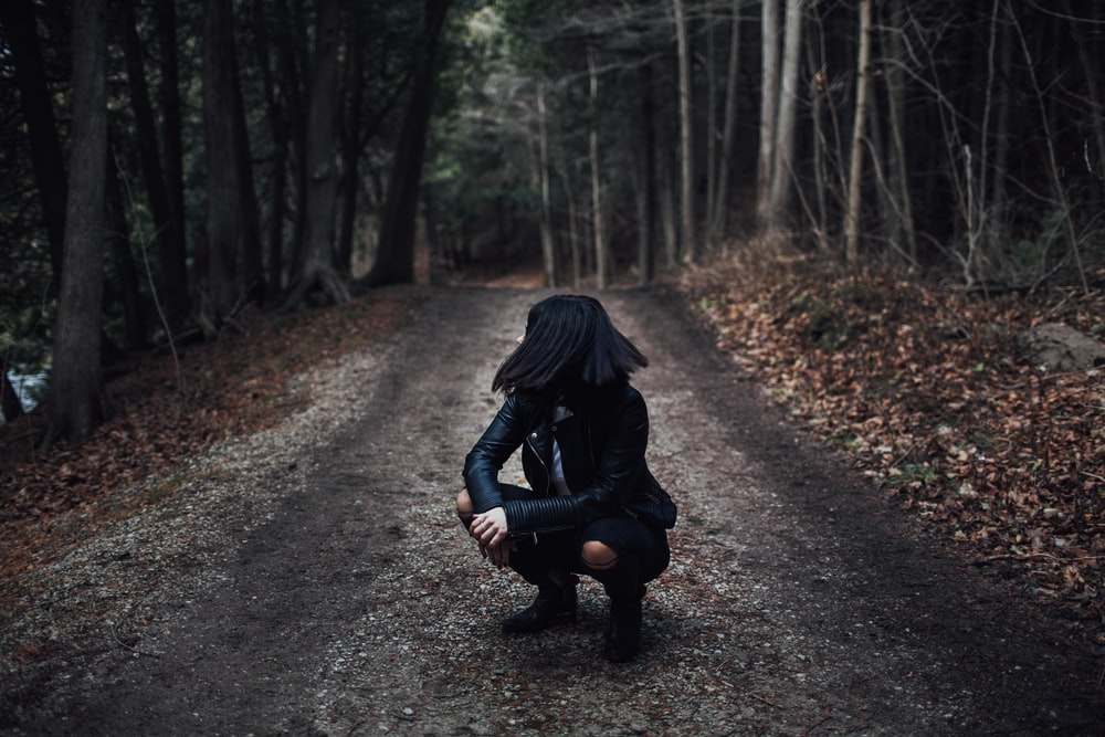 woman squatting on gray dirt road surrounded by trees
