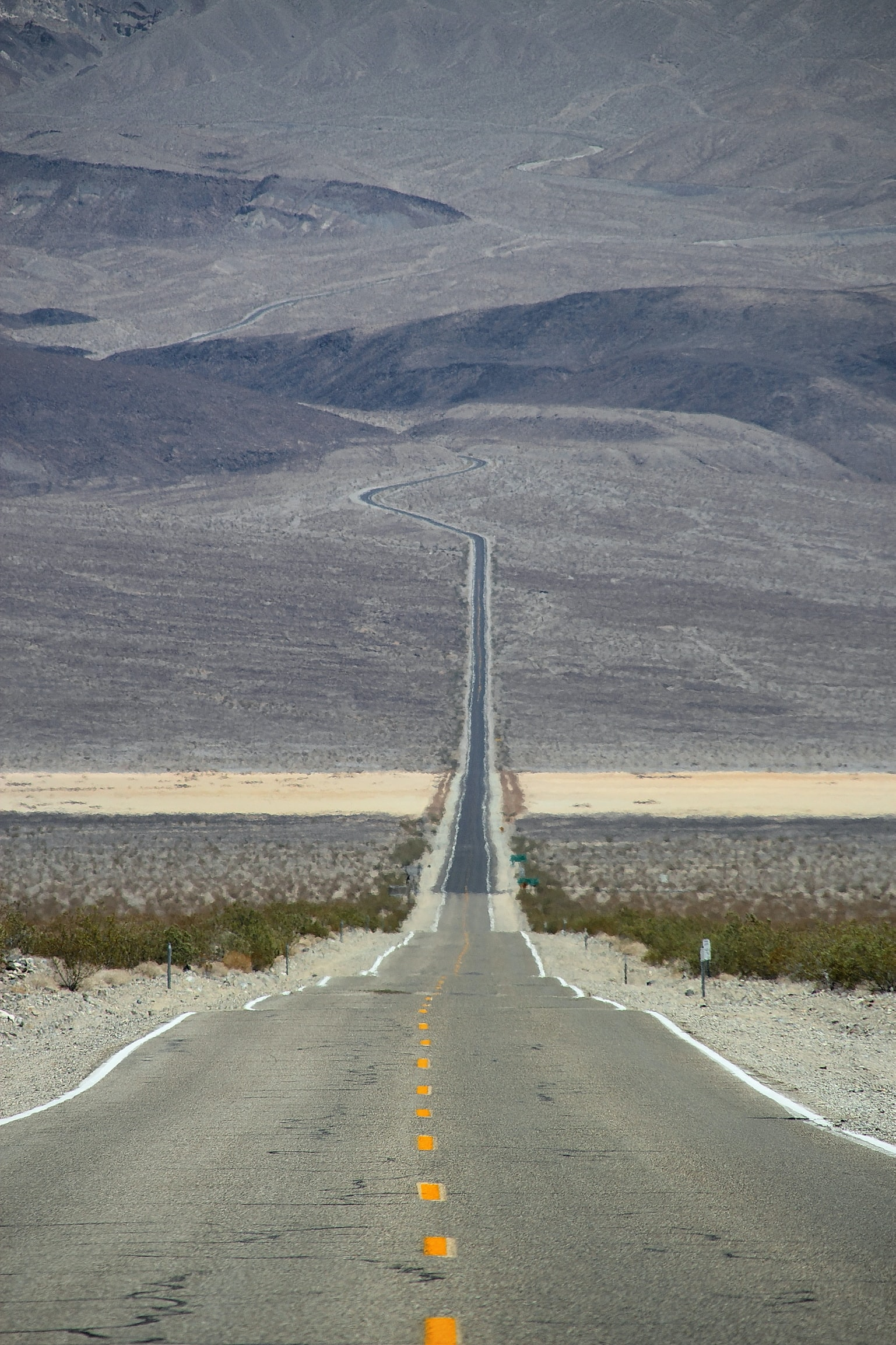 Empty rural highway road creates a line through the desert terrain