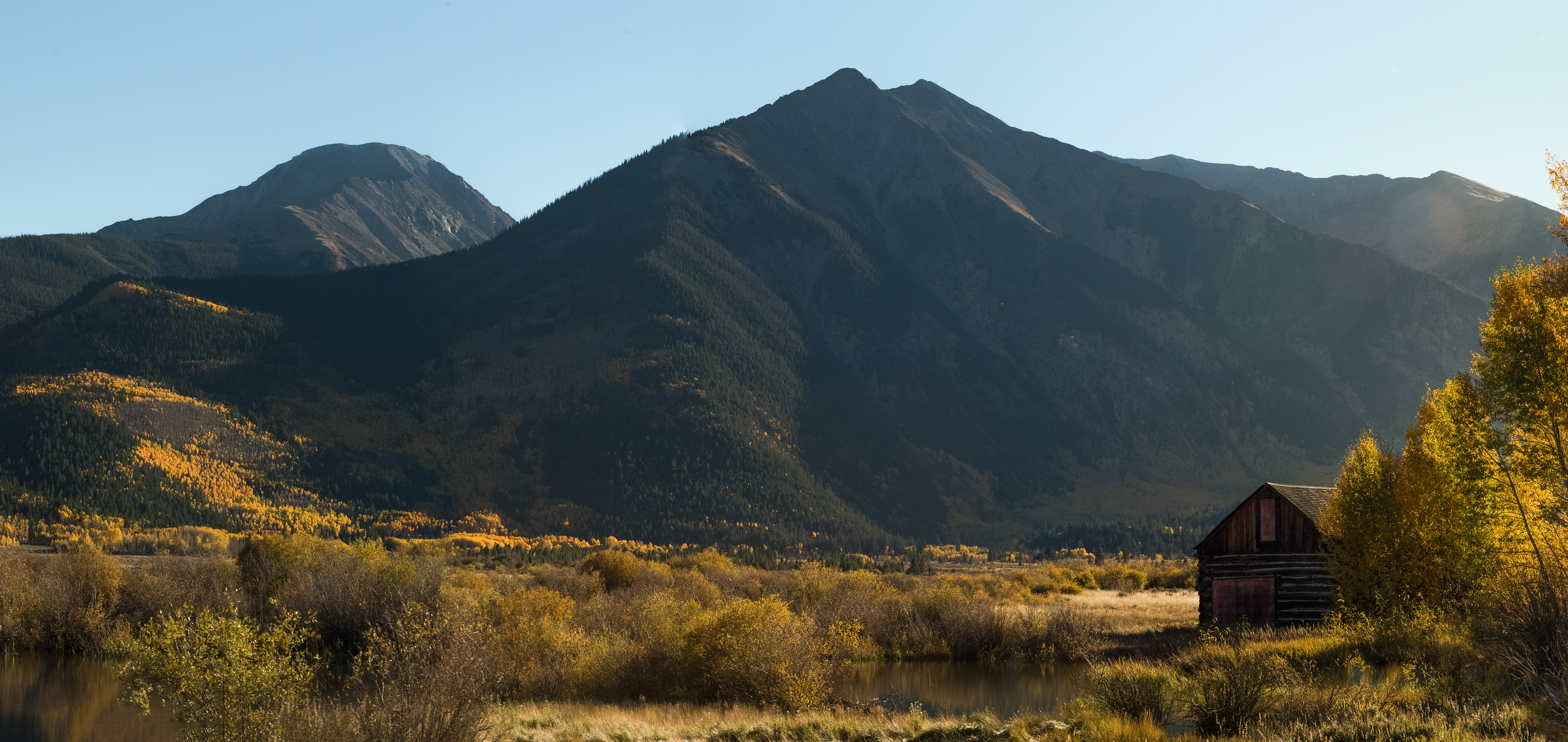 A mountain with glowing orange and brown trees at the foot beside a cabin.
