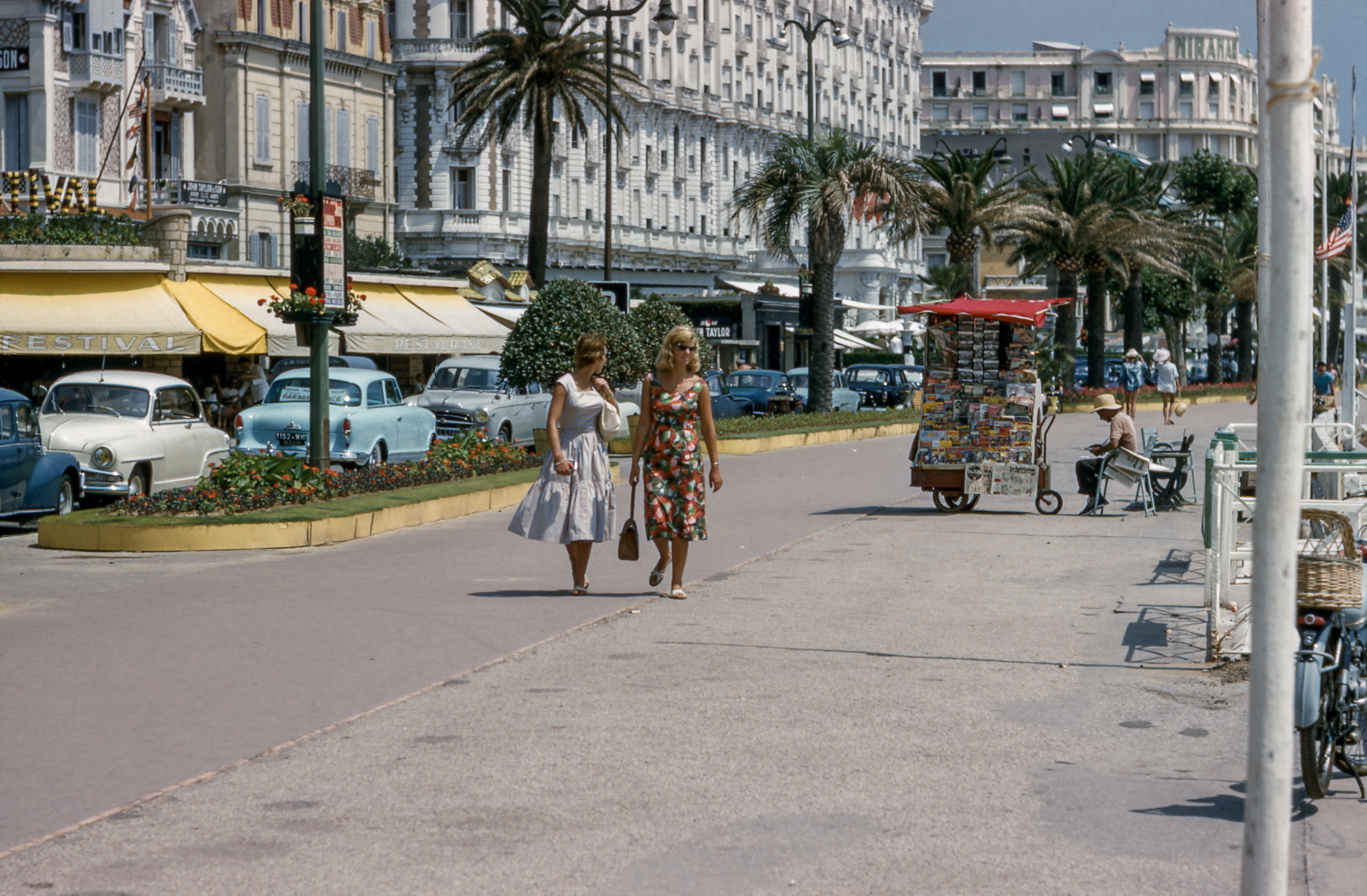Vintage shot of women in retro outfits walking down a tropical street