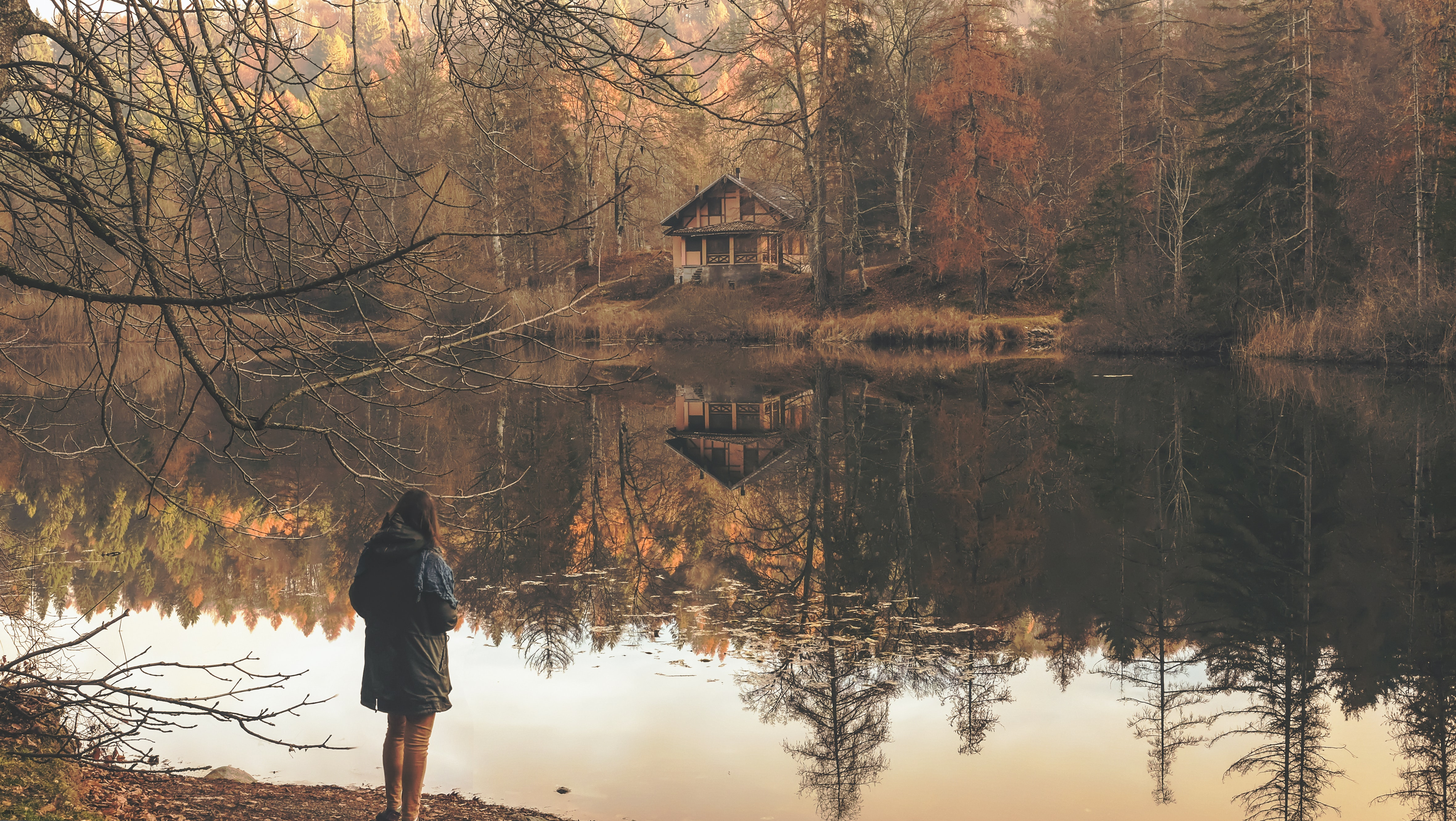 A woman standing on a lake's shore looking off into a cabin on the other shore