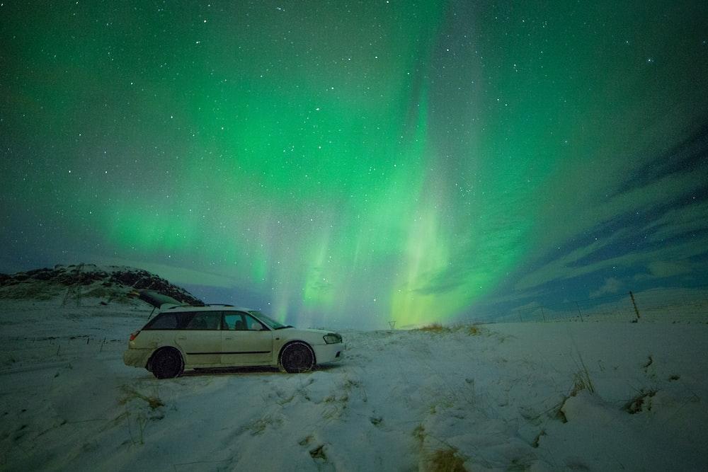 white station wagon under aurora borealis