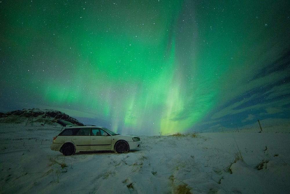 white station wagon under aurora borealis