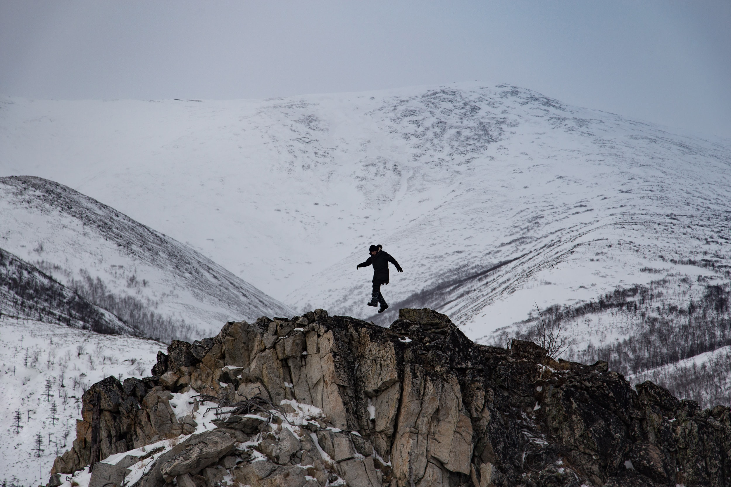 Person jumping on rocks on cliffs covered in snow