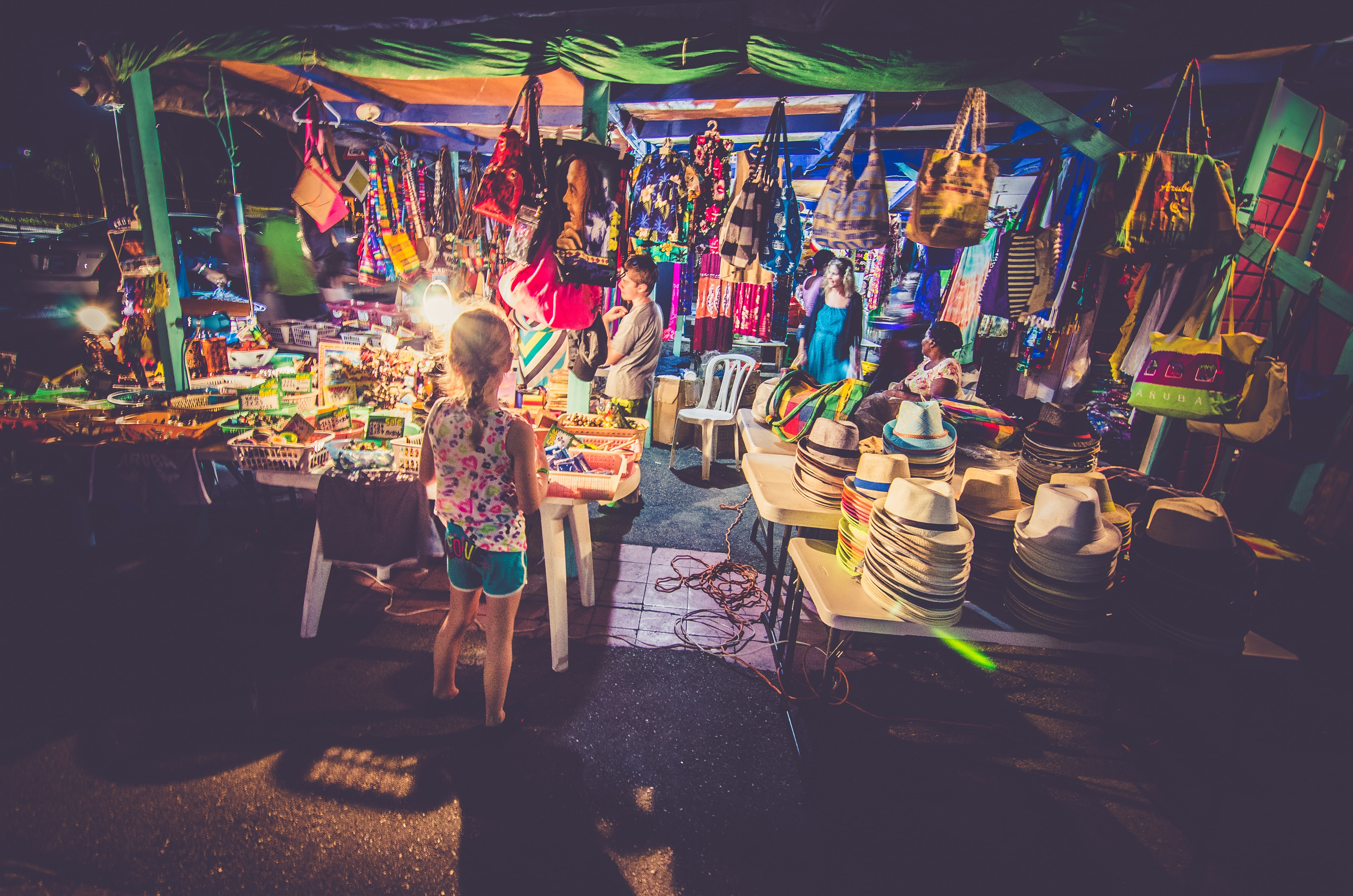 Children browsing the goods in a street market in Aruba at night