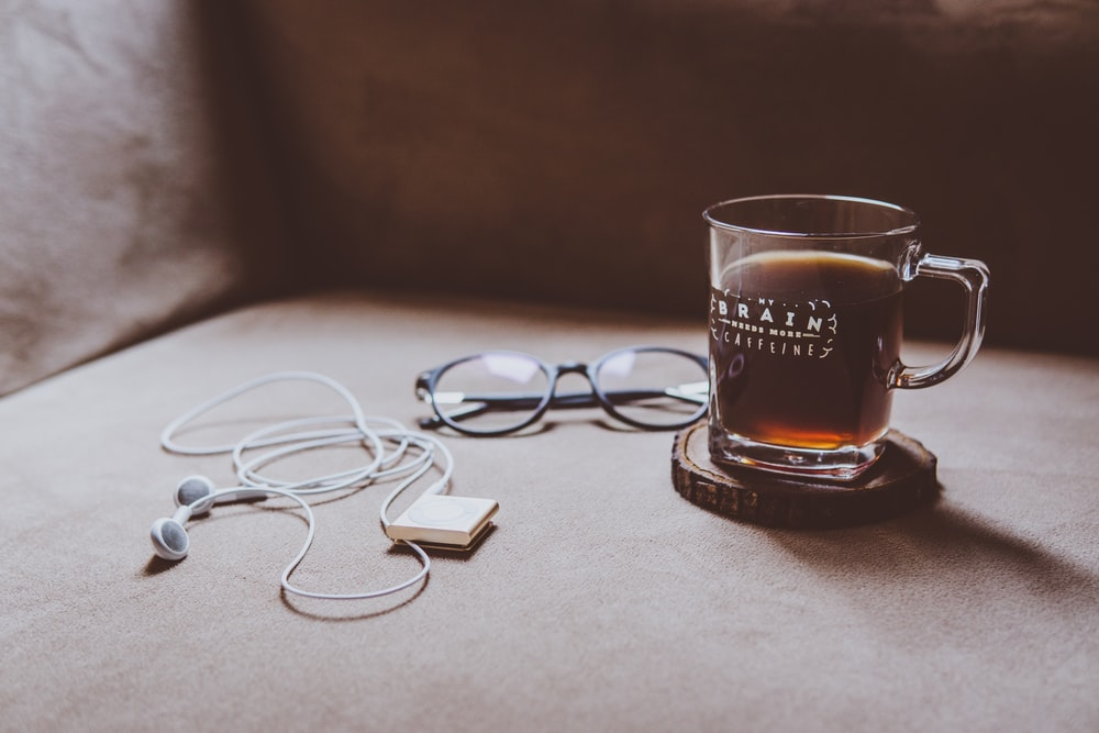 clear Brain printed glass mug on brown wood slab coaster beside black framed eyeglasses and white earphones