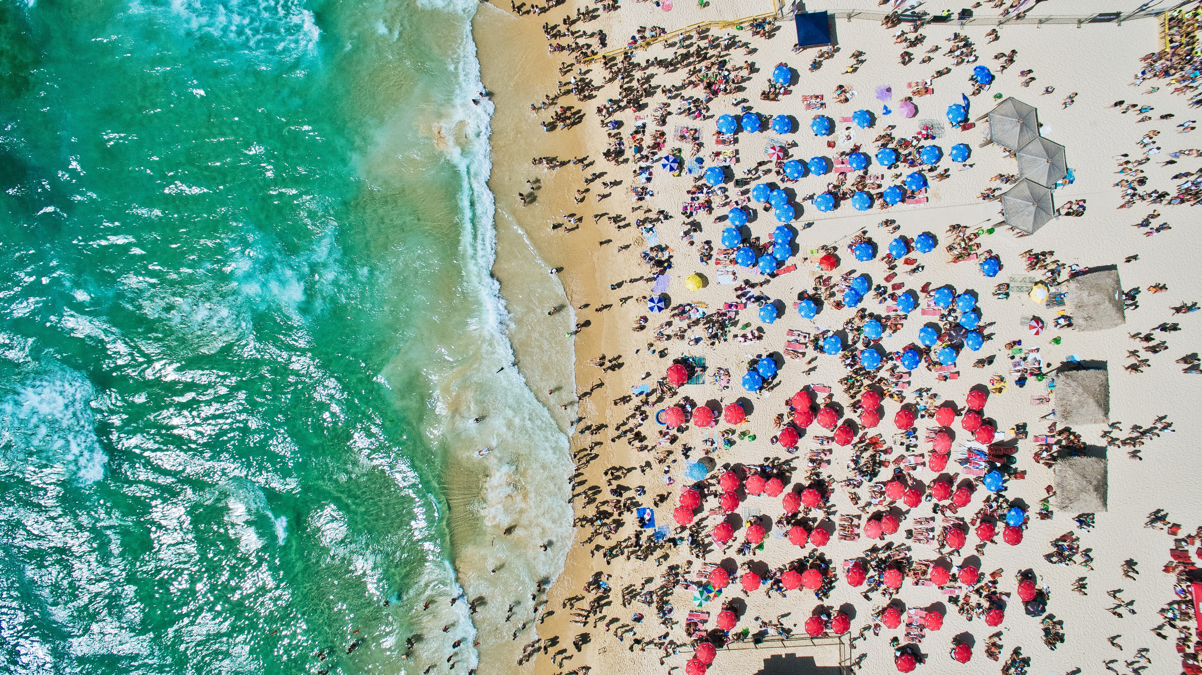 An aerial shot of a crowded beach with vacationers sheltering from the sun under red and blue umbrellas