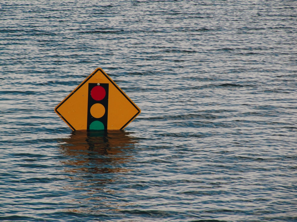 traffic light road sign partially submerged in deep flood water