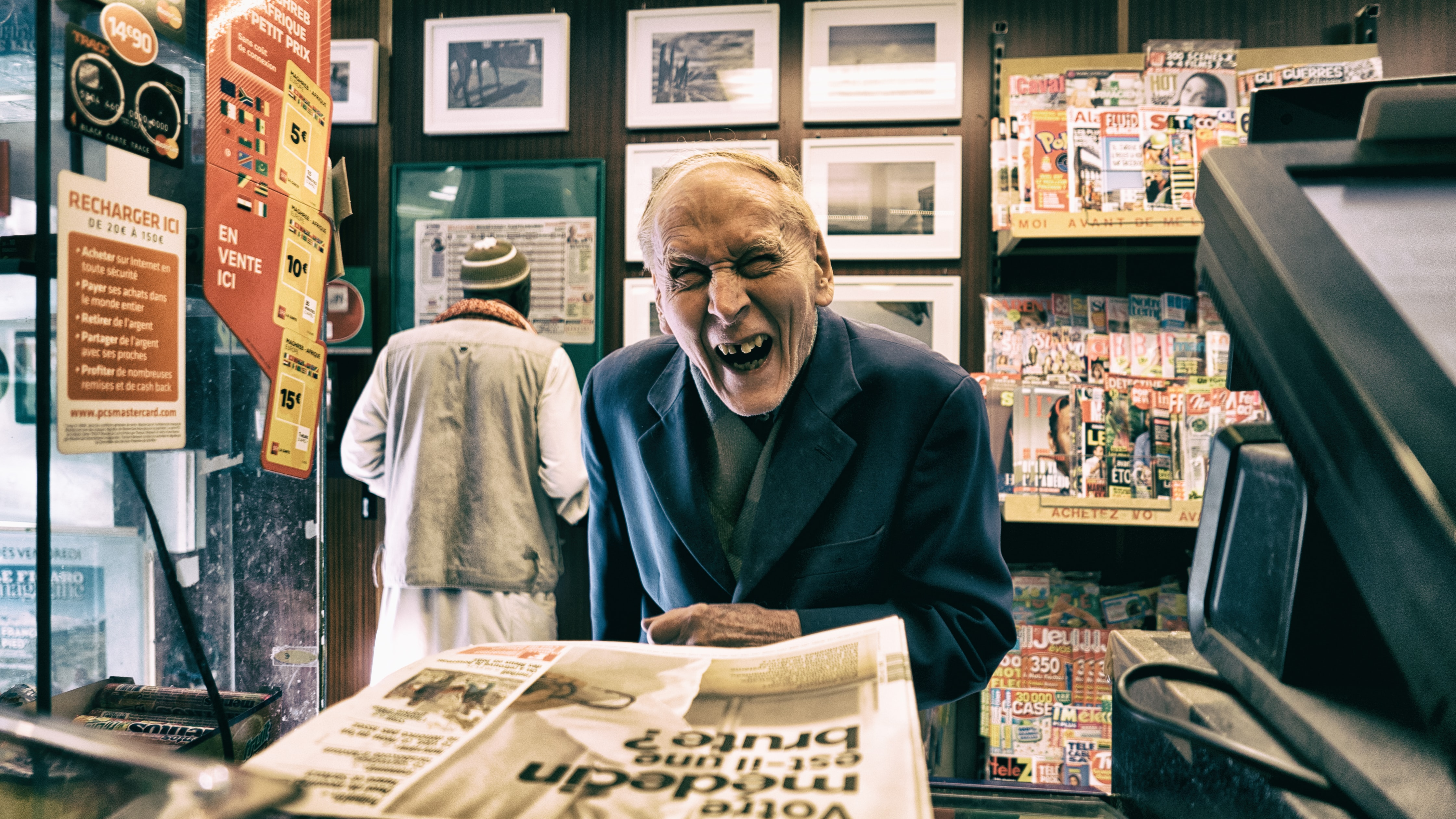 An old man giving a smile at the counter of a newspaper shop.