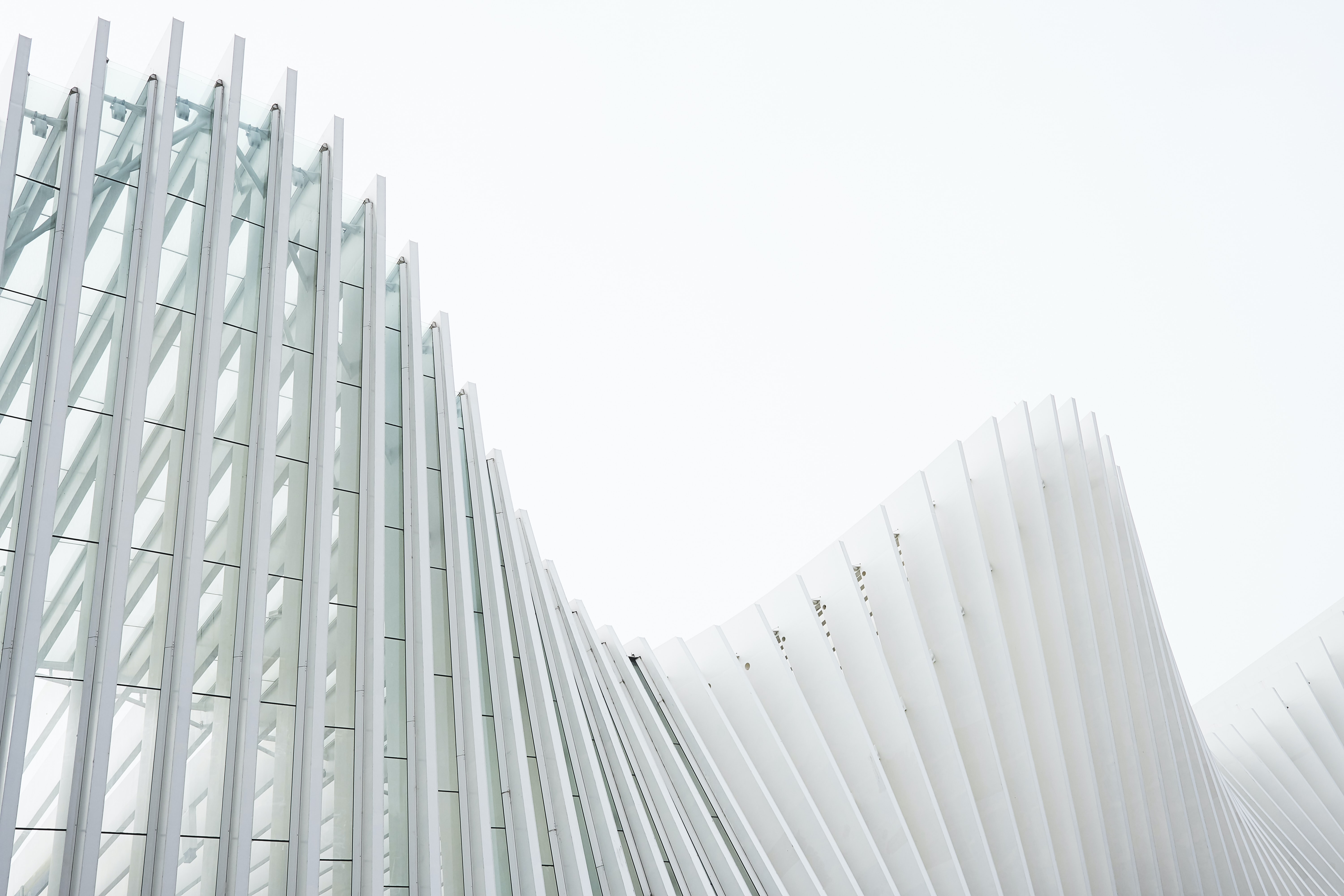 White concrete ribs in the undulating glass facade of a modern building