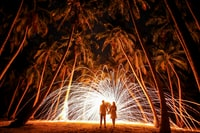 steel wool photo of couple holding hands under palm trees