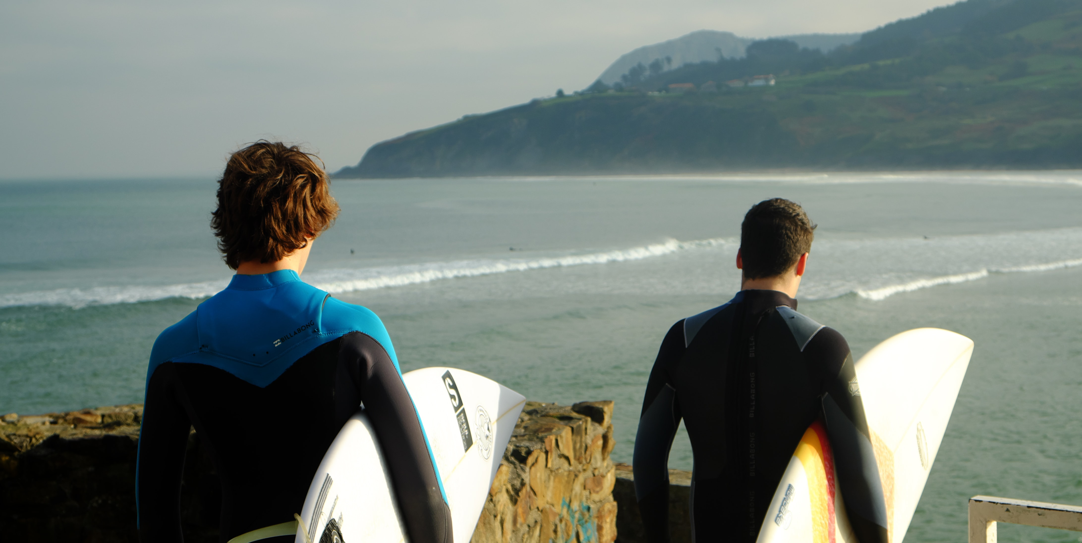 two male wearing wetsuits holding surfboards standing nearby each other on top of hill with view of beach below