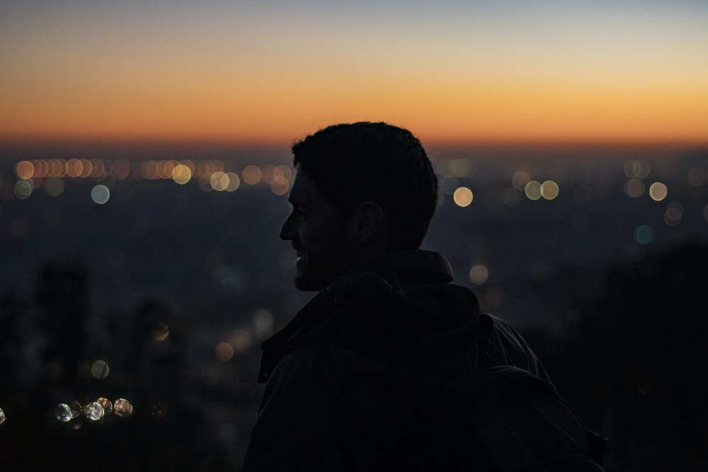 man on high ground facing right looking at city during nighttime