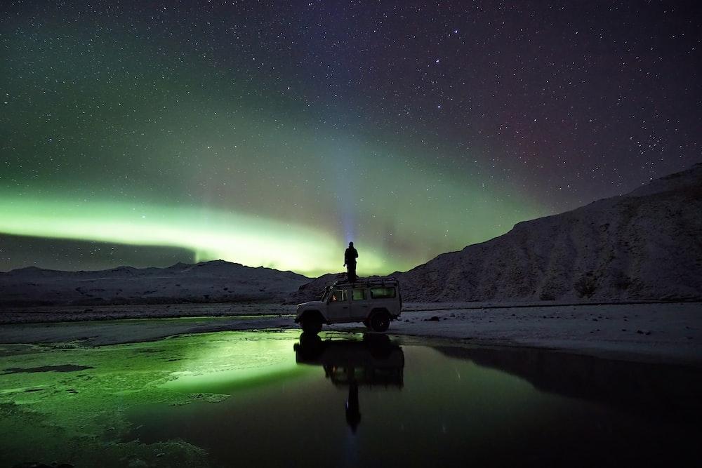 man standing on SUV watching northern lights