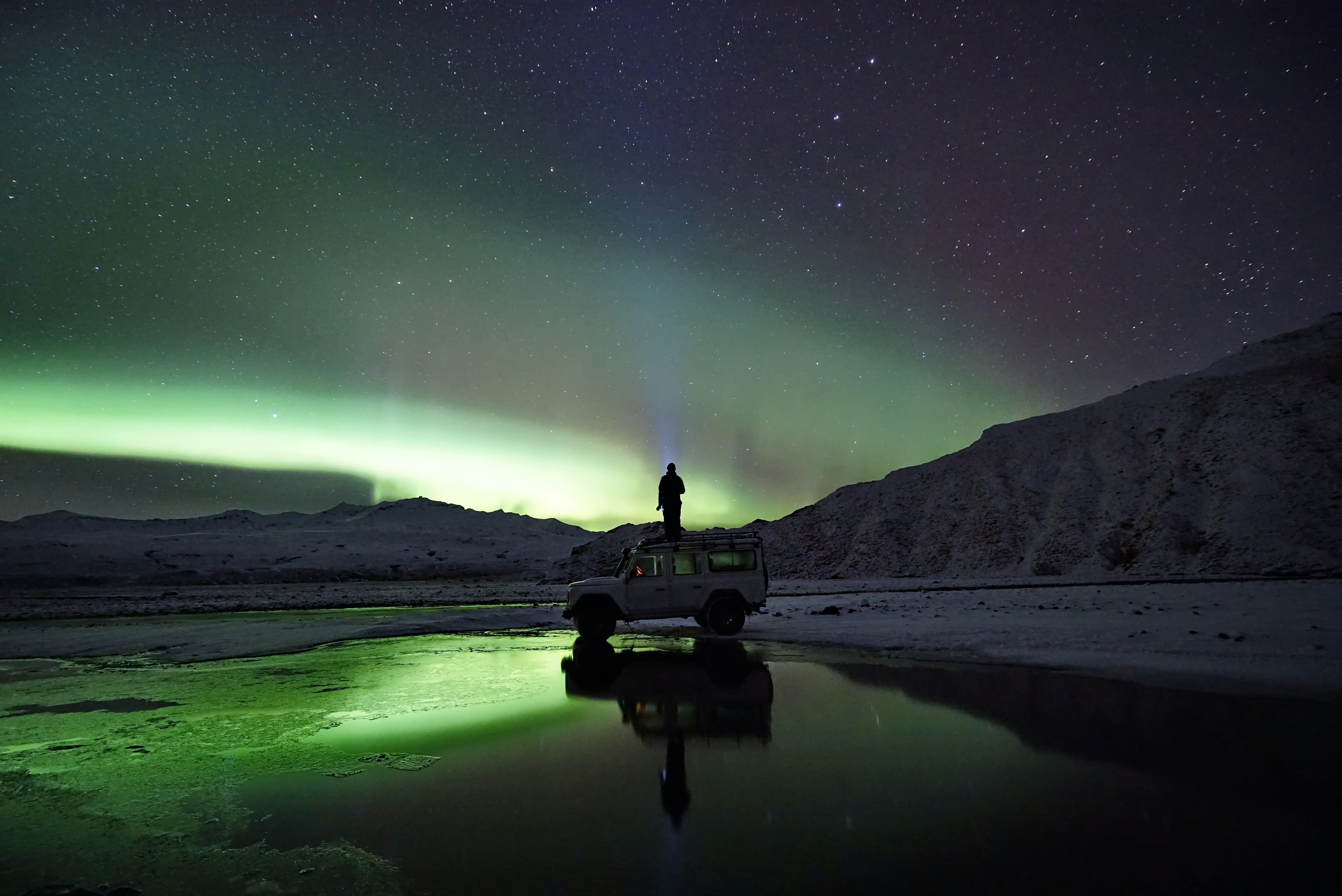 man standing on SUV watching northern lights