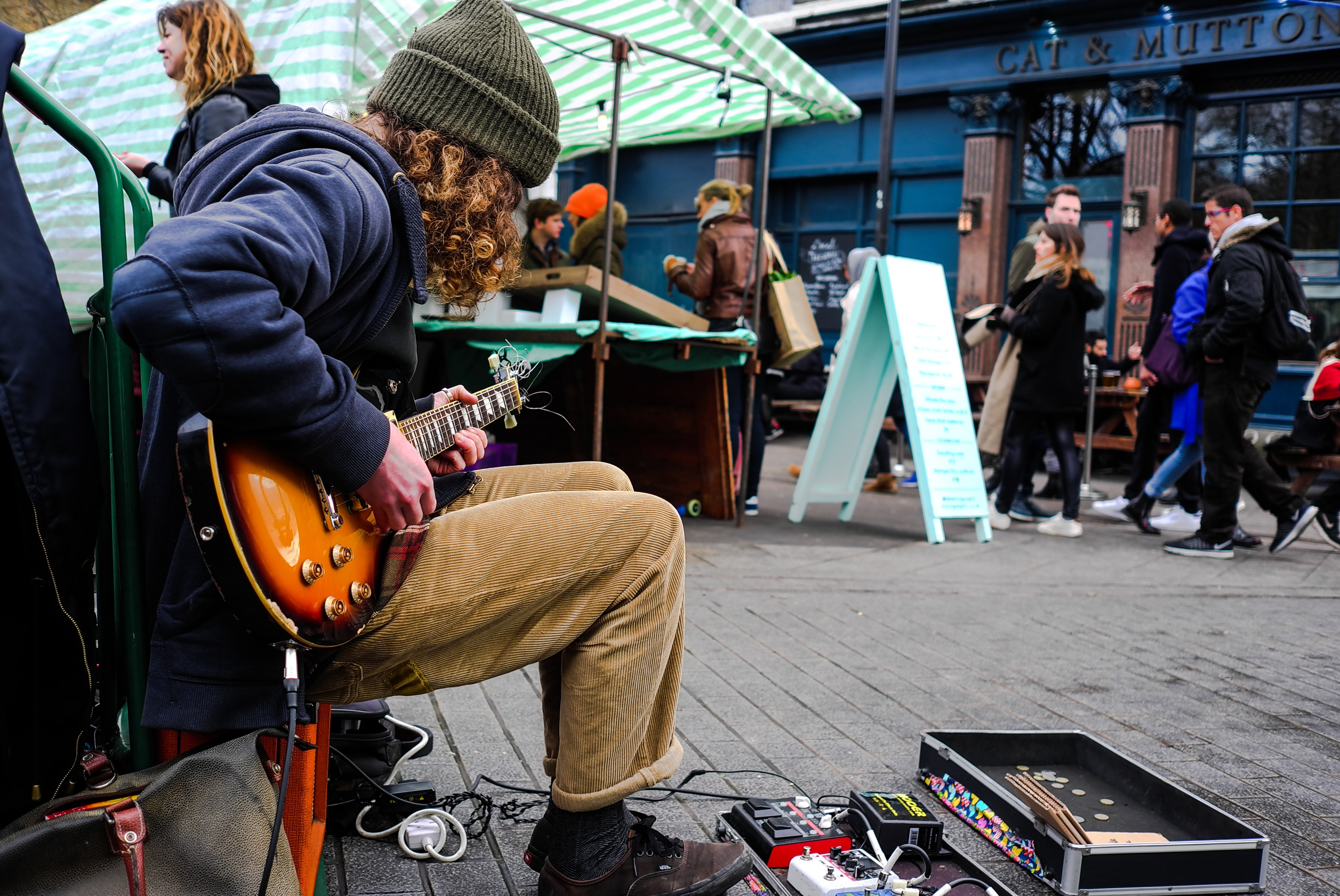 A young man in a beanie with an electric guitar busking in London