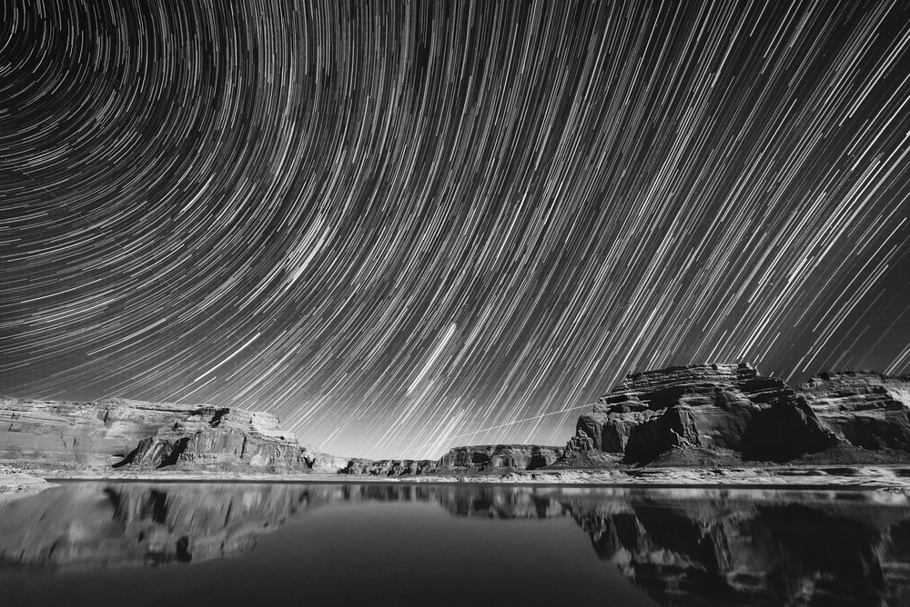 grayscale photography of calm body of water under sky