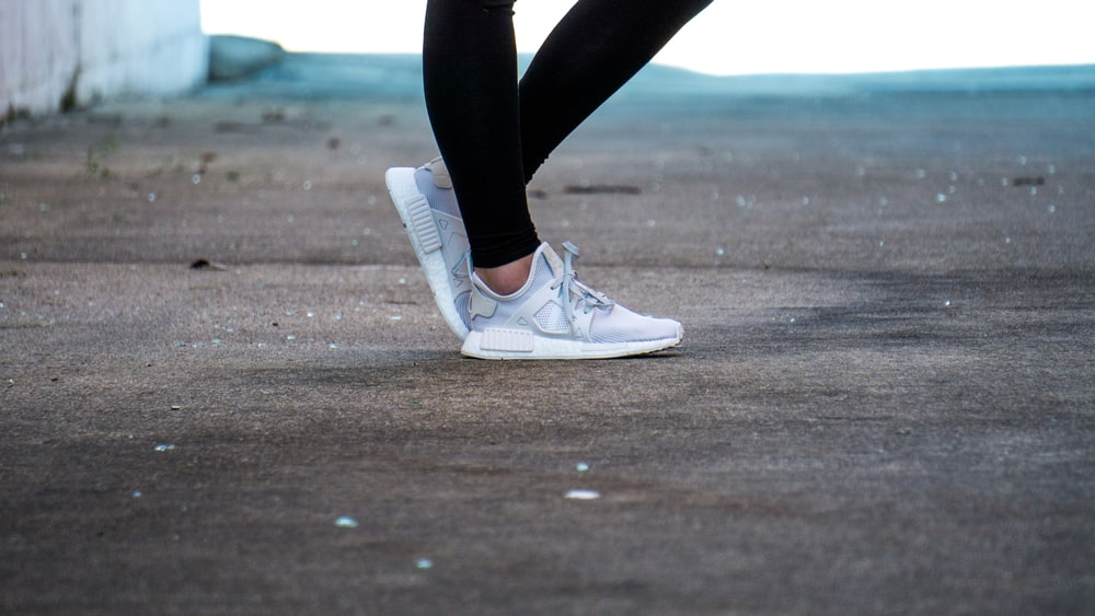 shallow focus photo of person wearing gray running shoes