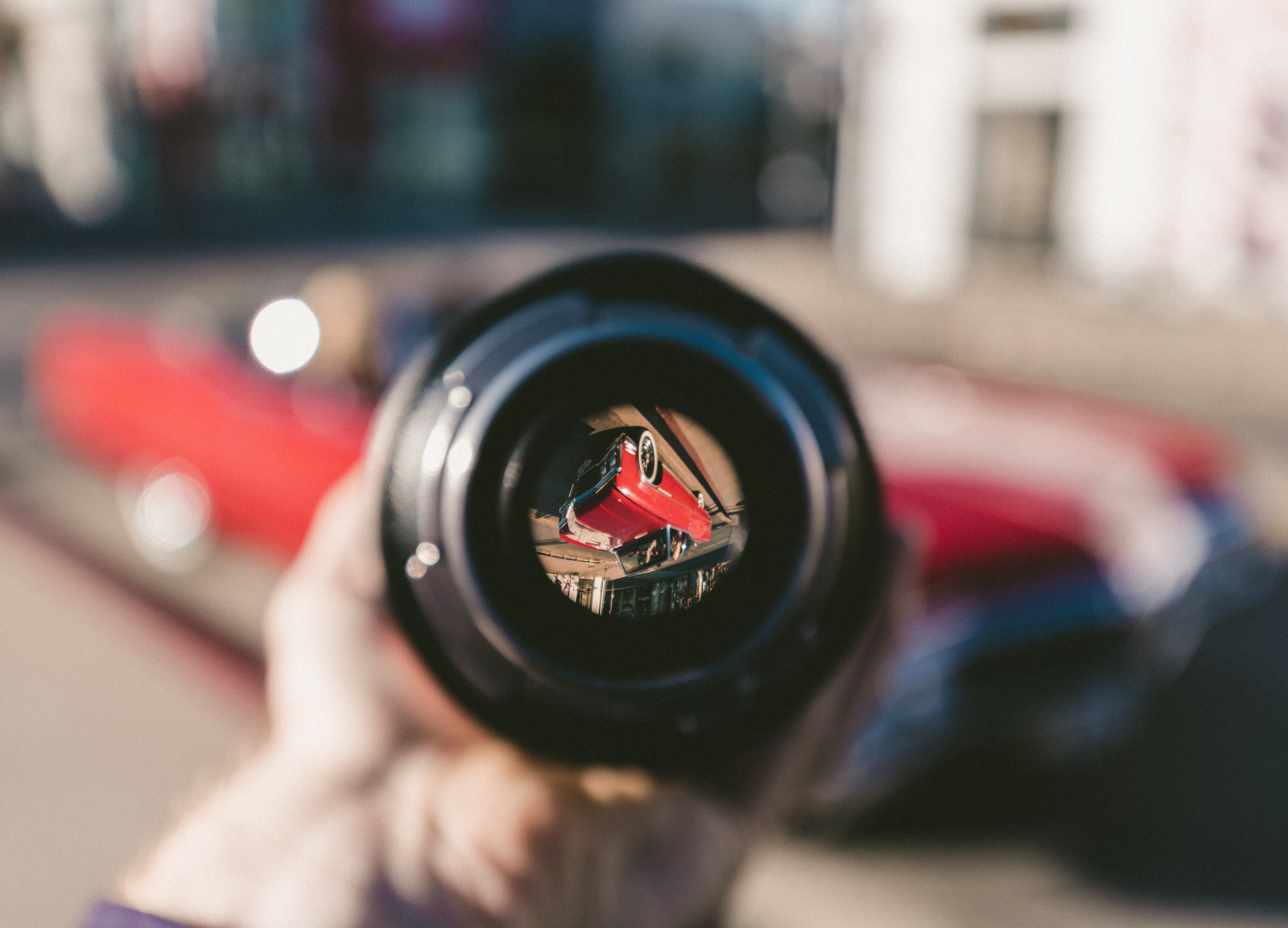 A classic red car looks inverted through a camera lens in Los Angeles.