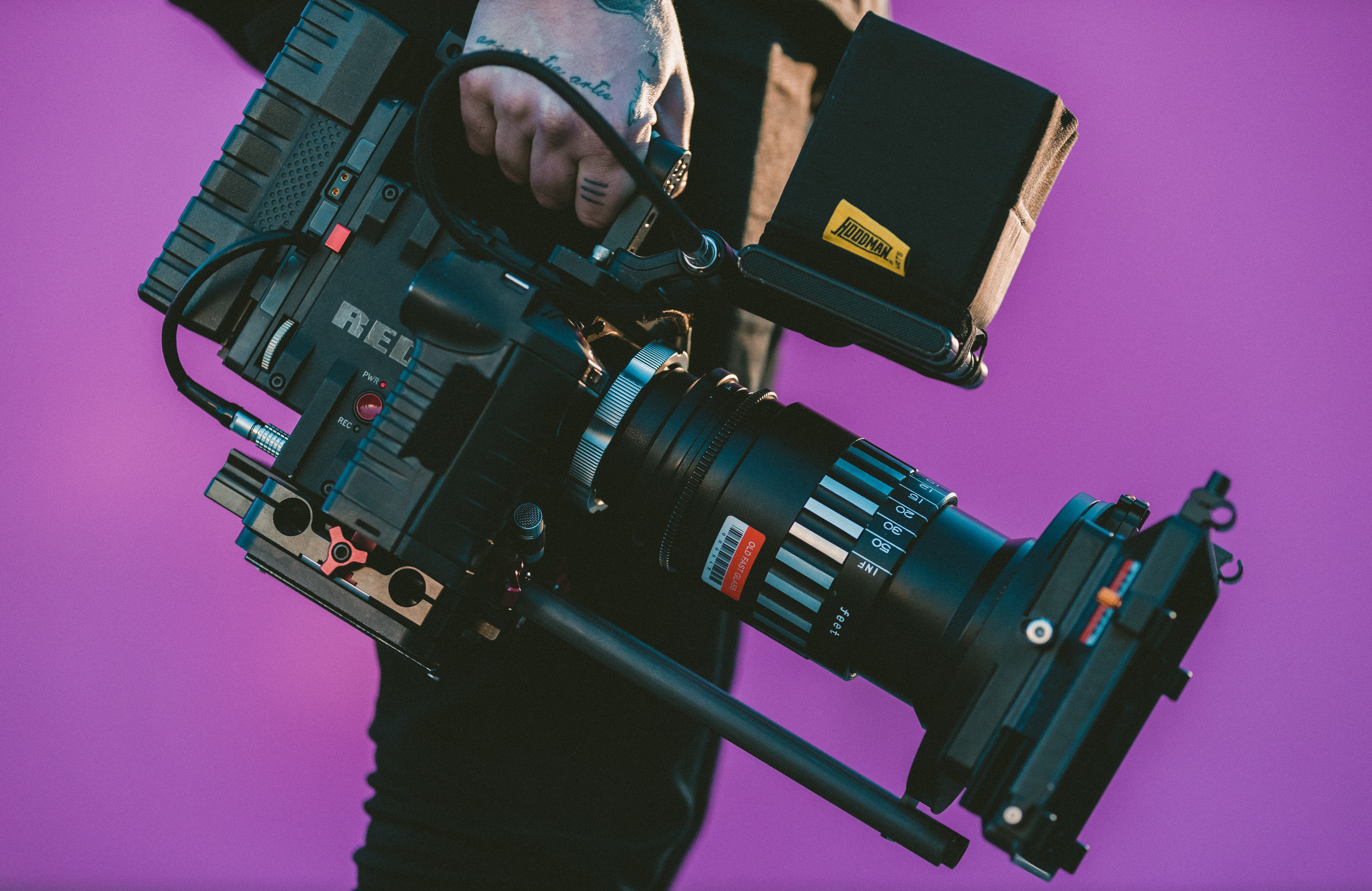 A close-up of a man's hand holding a RED video camera against a purple background