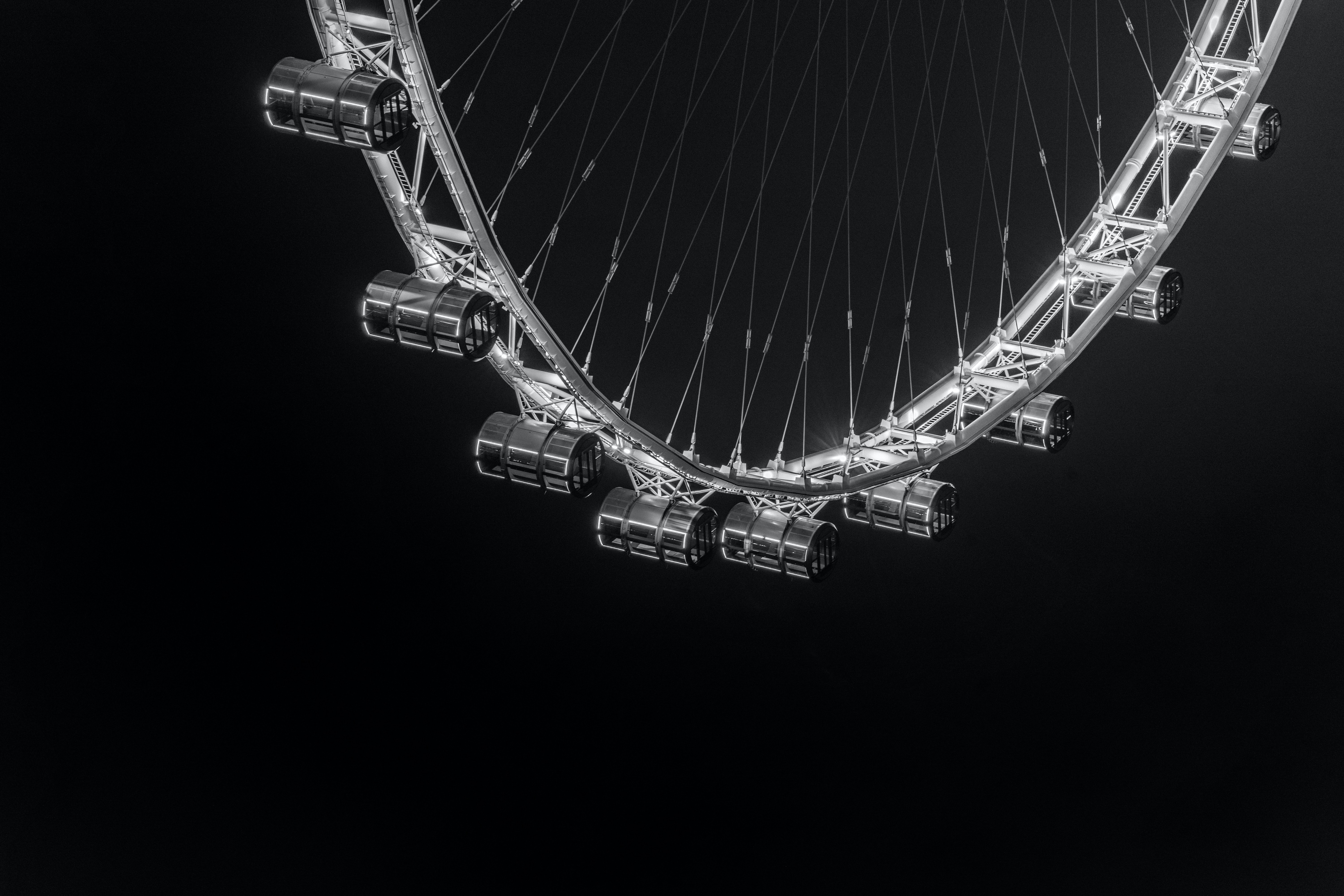 A black-and-white shot of the Singapore Flyer against the black background.