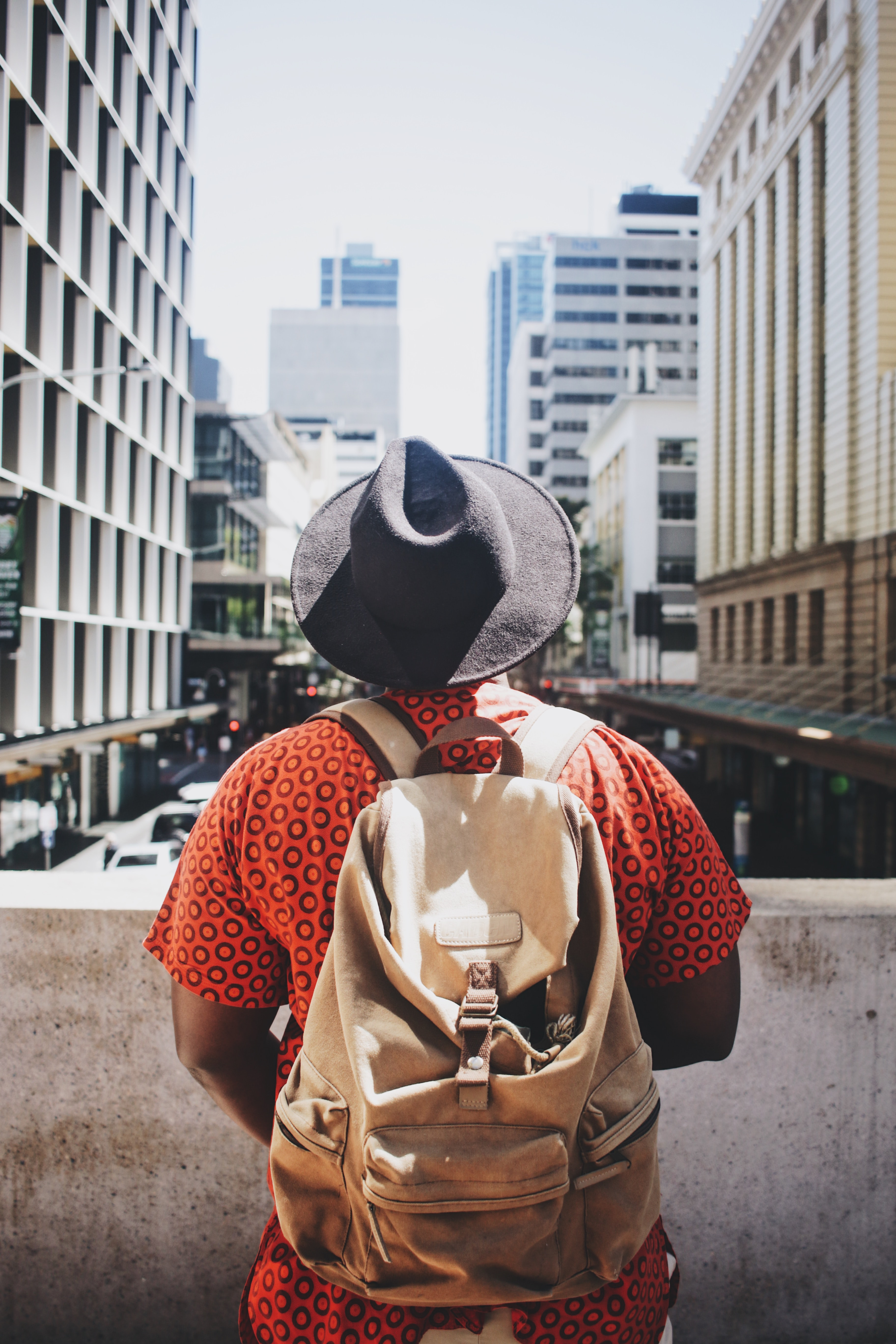 A man wearing a bright orange shirt, hat, and backpack looking out on the street in Brisbane City