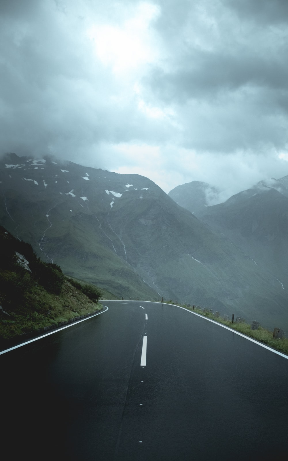 gray concrete road between green mountains under white clouds during daytime
