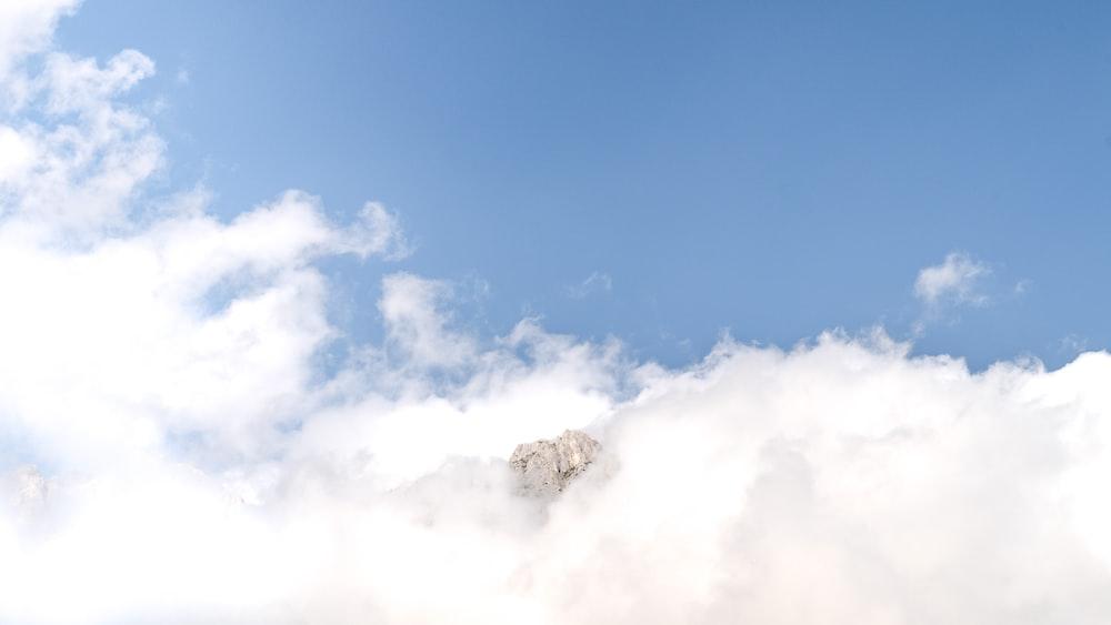 mountain between clouds