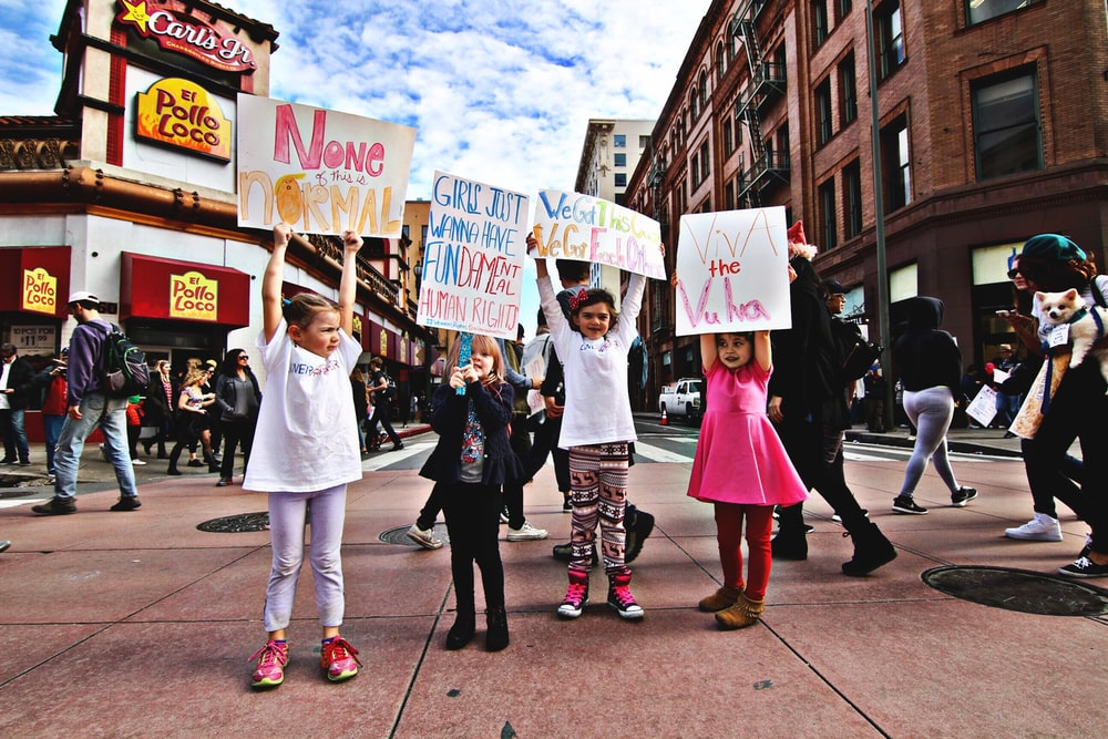 four children raising up a banner at the middle of a busy street during day time